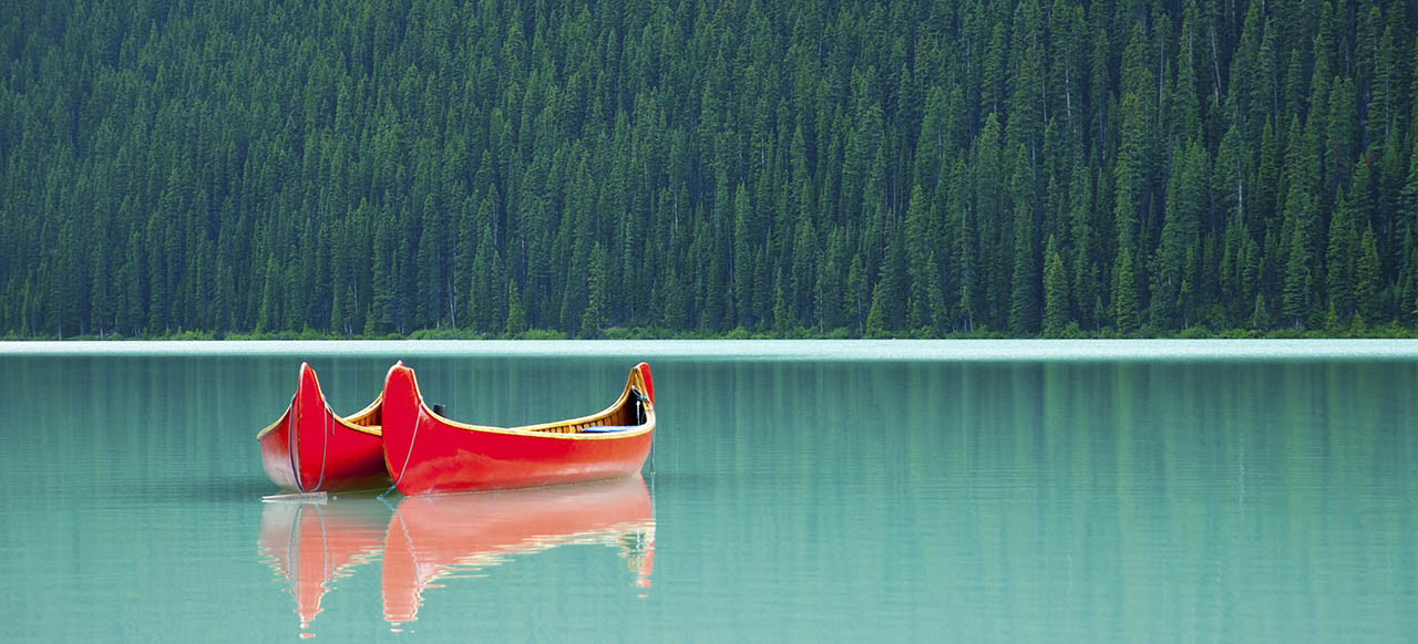 Image of two canoes sitting next to each other on a calm lake with trees in the background