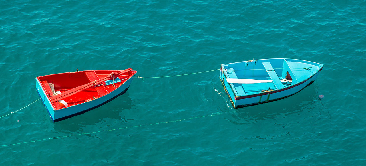 Image of one row boat pulling another row boat