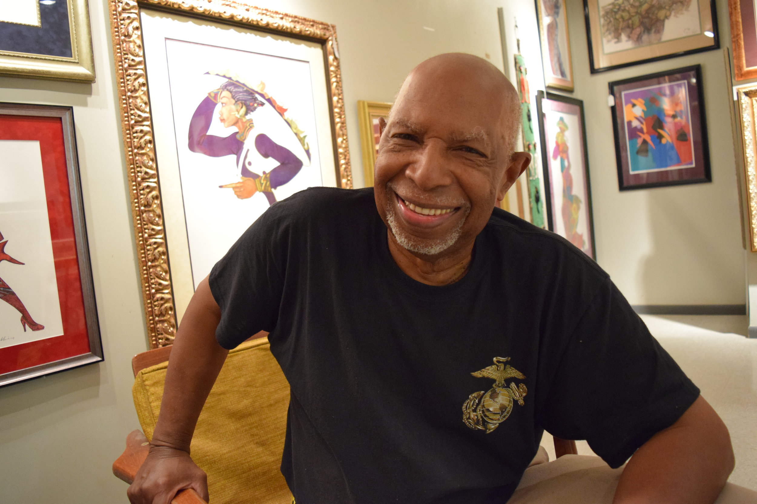 """Lawrence Calvin D'Antignac (aka """"Dan"""")   Owner,The Woodshop   """"I've owned this business roughly 42 years. Most of the art, I guess about 50/50 comes from the United States and Africa and the Caribbean. [I got into this business because] I needed a job. I'm a cabinet maker, a self-taught cabinet maker. I opened this shop up to make furniture. That's the name of it, 'The Woodshop'. I had three boys that were in the Boy Scouts. They had a project to do one time. The Scoutorama was coming to Chicago, and the theme of it was 'your hobbies'. At that time, Hank Aaron was breathing down Babe Ruth's back to break that record, and the boys were collecting sports' pictures. That was their hobby, and they wanted to display their sports' pictures. They didn't know how they would display it. They said they would thumbtack them to the wall. One of my sons said, 'Why don't we put them in frames?' I said that was a good idea. They had about 150 pictures of basketball, football, and baseball. I said, 'Okay, I'll go to the store and get some frames.' So I went to Walgreens to get 7 x 14 inch frames, and they was four dollars and something a piece. So, 150 times four dollars and something a piece, I decided I wasn't going to pay that kind of money on a one shot situation (laughs). My youngest son said, 'We can make the frames.' I said, 'That's a good idea.' So, I went to see if I could get some stock to make the frames, and the only place I knew to go was a frame shop on the North Side. I went to about two or three of them, and they wouldn't sell me the stock. They wanted me to buy the frames from them. So, I went to one place and asked the guy, and he said, 'No, we don't sell the stock.' There was a Black guy that worked there. He came out the back door and said, 'Hey, I know where you can get some stock. You go over here on Halsted and something, something.' I went over there and the man sold me everything I wanted. And then he told me where to get the glass from…So I got the glass, """