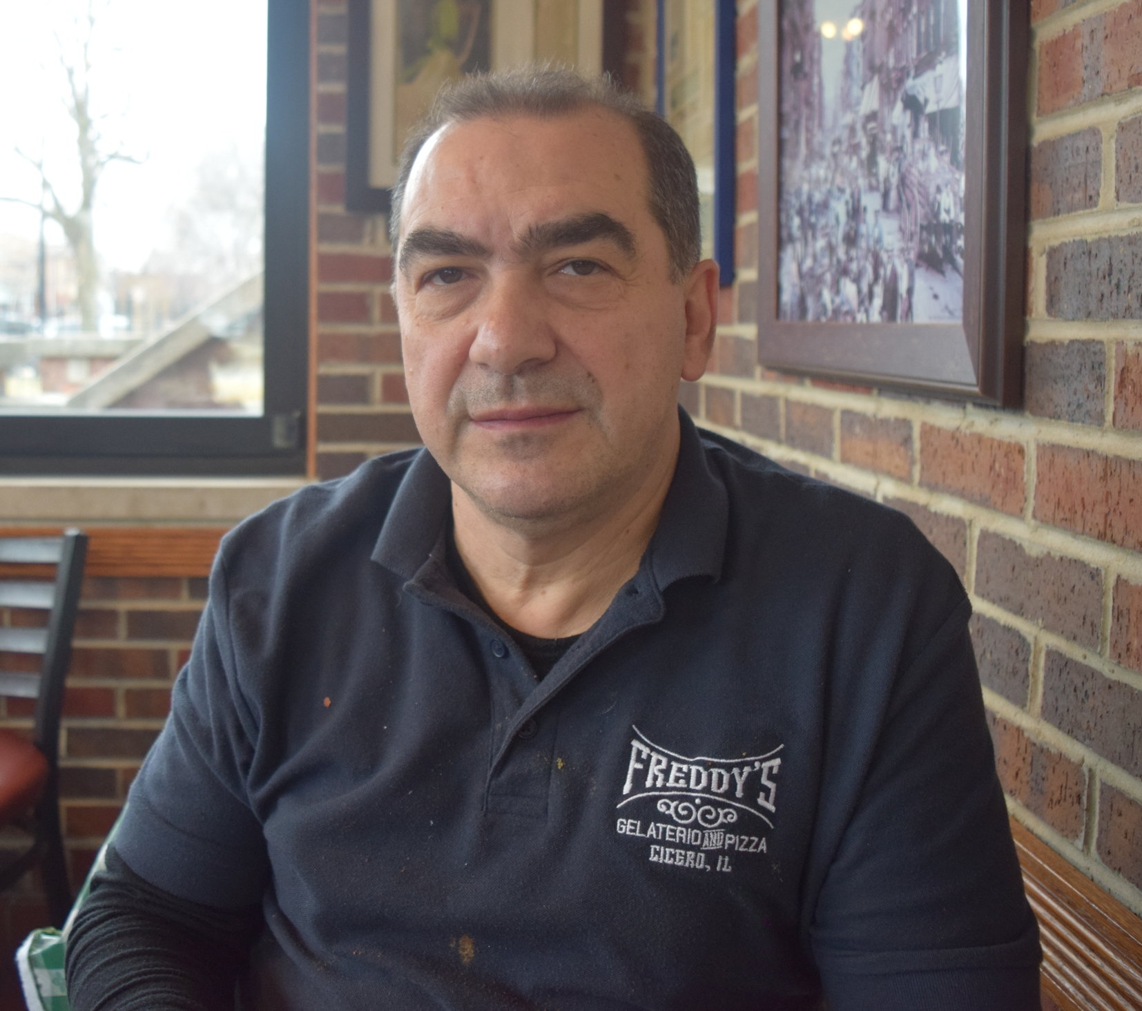 """Giuseppe Quercia   Owner, Freddy's Pizza   """"I started working here [the original location] in 1968. I came from Italy. I was 13 years old. I started cleaning, washing floors, pots and pans. From there, I graduated to make pizzas and make Italian ice. After I finished my senior year of high school, the place was up for sale, and I purchased it. That was the establishment here where we are now. And that was it. I made a lot of changes. We added on a deli, Italian lunch meat, Italian products. Before it was just a lot of things to survive – it was a 2-3 person operation. Now we have about 10 or 11 people working for us. This all started in 1973. I went back for my first trip back to Italy in 1978-1979, and I brought a lot of ideas that I see there like the trattoria style and the gelato. When we started, it was a little rocky road because people were not aware, but now gelato is very popular. I met my wife here too. We both took an adventure and got married in 1983. From that point on, we build on, build on, and build on and became a place to stop. Last week, there were some customers who stopped in who wanted to see me and talk to me, and I realized they were the 4th generation [of the family] I am taking care of. Next March, it's going to be 50 years I've been doing this. Some of these kids are coming here, well I call them kids, but their grandparents used to bring them here. Now they're bringing their kids, and some of their kids are getting married. For a little small place, you see very few places like this. New York you see a lot of them. But here, it seems like in Chicago everything is commercialized. Everything has to be big. These ma's and pa's are dying out. There's a love and a lot of dedication into this business. It's rewarding too at the end of the week. We were able to show people beyond meatballs, pasta, and spaghetti, there's more other Italian foods. It's a beautiful atmosphere when you come and see all these people that you know – such a great feeli"""