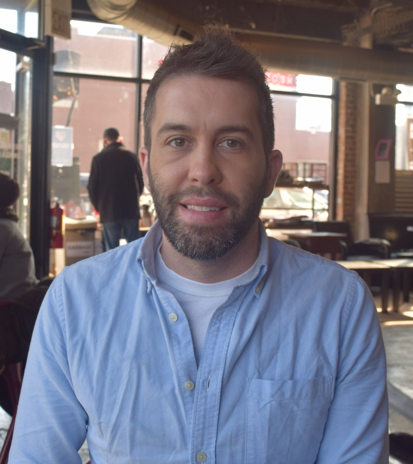 "Jake Sapstein   Co-owner, Robust Coffee Lounge   ""Robust Coffee Lounge was started between my husband and I seven years ago. It was at the time the financial markets were crashing, and both of us knew we were going to be out of work. It was an idea that we had that we thought would be something we'd do in our retirement, but it was the only thing we could see to do at that moment, so we decided to go for it. What brought us into the neighborhood was a couple of different factors. One is that the building that we're in, I was working on with a developer at the time, so I knew the building. As far as considering the neighborhood, my grandparents ran a chain of pharmacies on the South Side for 50 years, so I spent a lot of time in the neighborhood. I used to work at 83rd and Cottage Grove at a pharmacy that was there. That was kind of like my summer job. So, at the time we looked around, and it was pretty obvious that there was a lack of food, lack of drink, so it came down to what would be the best food based business to go into. Coffee is something that everybody can kind of partake in whether they were part of the neighborhood, part of the university - whether they were a young student or a grad student, a kid or retired adult, if they have money or are living on a fixed income. Coffee is $1.50 – you can come, sit, soak up the atmosphere, catch up with friends, get work done, and so that was what we thought would be the best route to take in the neighborhood…There is a great amount of potential in this neighborhood. If you're in any other neighborhood, you may see dilapidated buildings. You may see open storefronts. You drive even through Lincoln Park, you find on a street like Armitage or Halsted where there used to be thriving businesses, open stores or for rent signs. Here we kind of had that at one point. There were riots and fires in the neighborhood, and it kind of cleared out quite a bit of the infrastructure. So, now people are coming in and actually able to start from the ground up, and I think that's got a lot of people excited."""