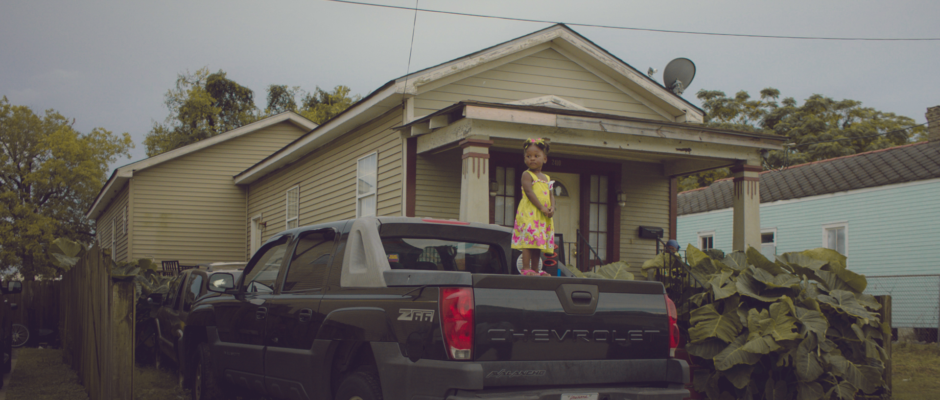 We had a big New Orleans parade setup in the downtown area. Afterwards we went out looking for New Orleans 'flavor', and found this girl who fit into a separate opening about how music brings together people, no matter where they're from, and starting when they're a baby. This little girl is standing on the back of this pickup with a speaker next to her.