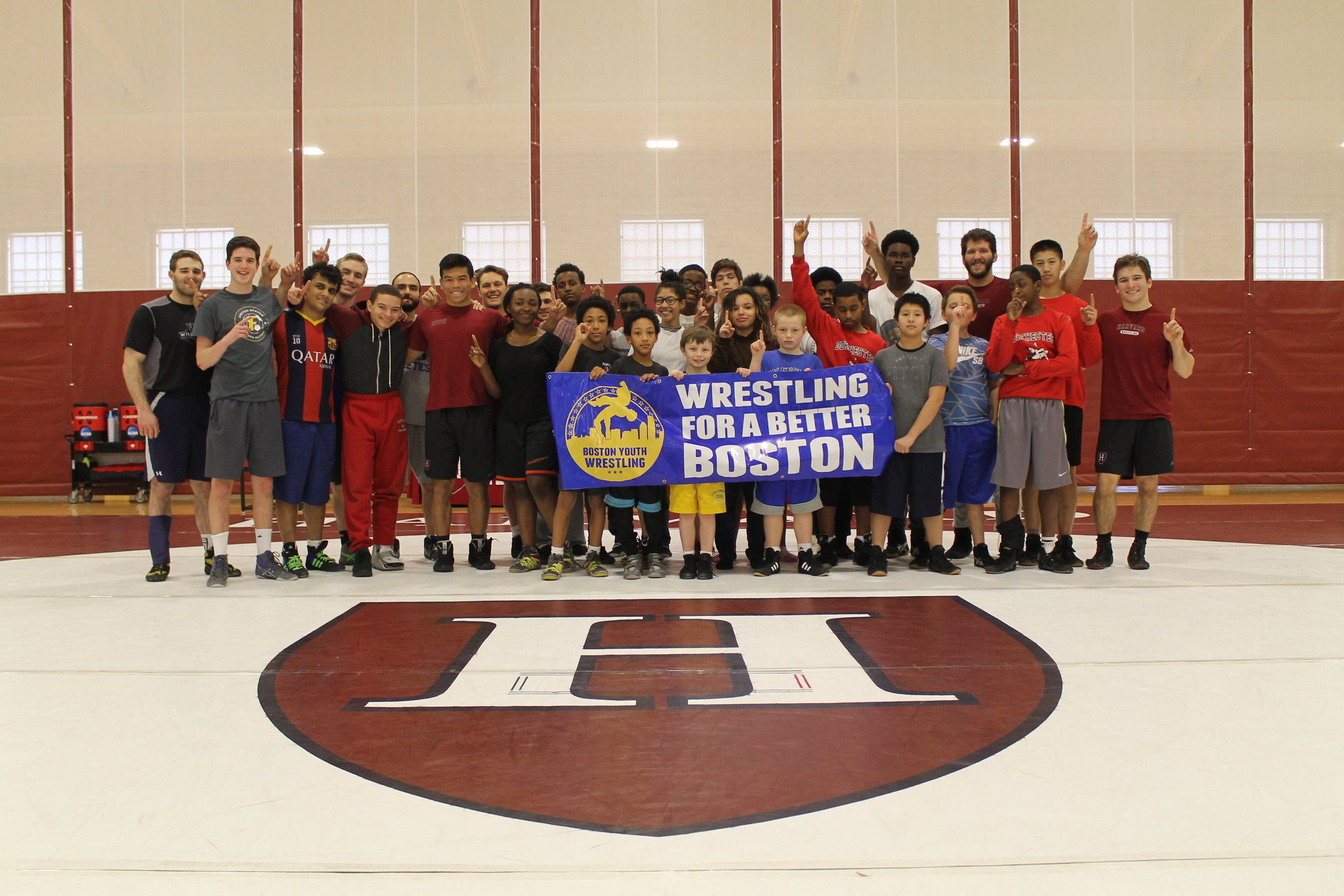 BYW student-athletes gather together alongside some of the Harvard Wrestling team's wrestlers and coaching staff for a picture at the Maklin Athletic Center in Cambridge, MA.