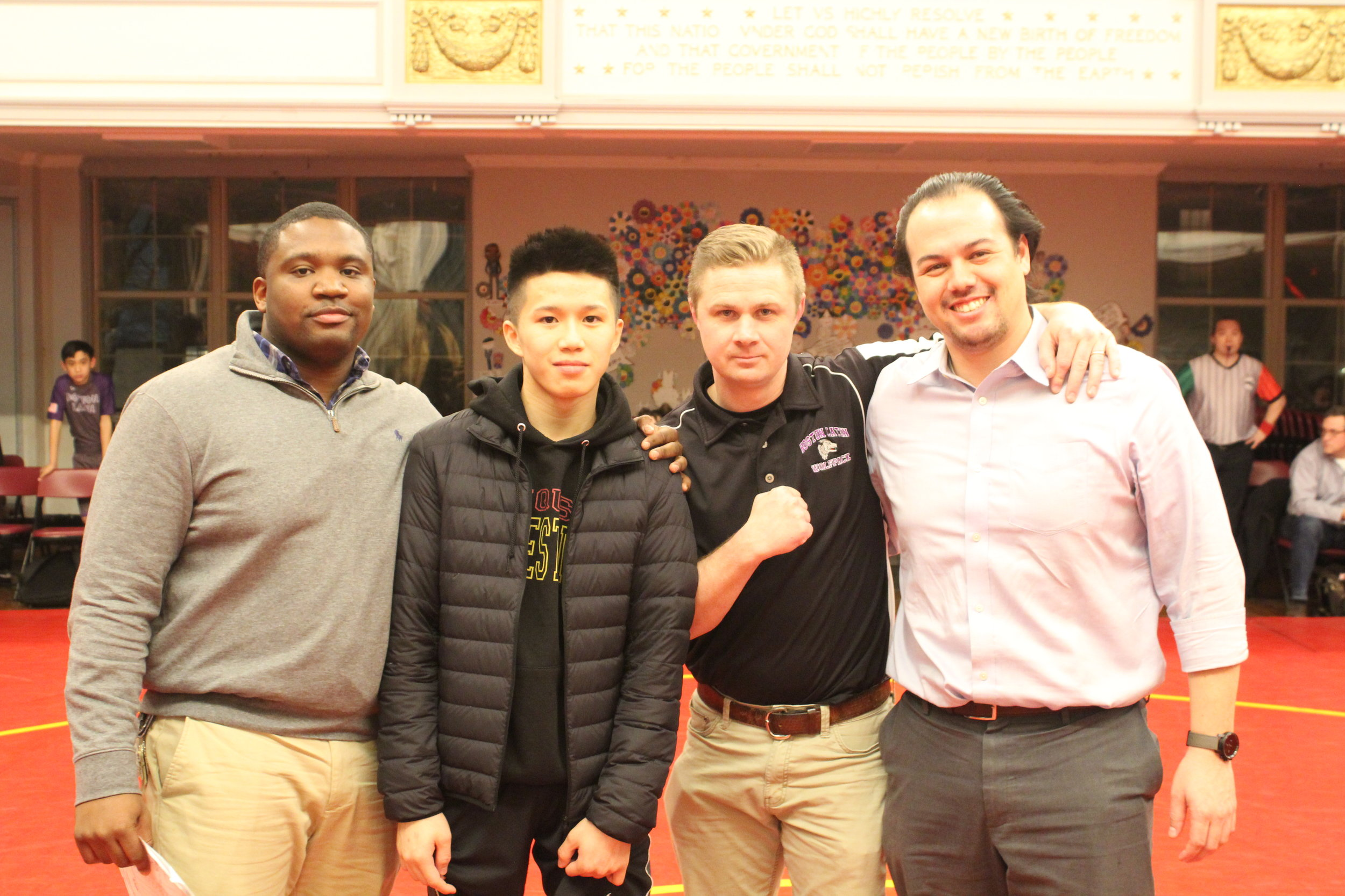"Ricky Sun was awarded the ""True Grit Award"" given annually to the wrestler who displays the grit exemplified by Huang Wei Speicher. Pictured with Ricky are Coach McKoy (JQUS), Coach Gibbons (BLS), and Josh Speicher."