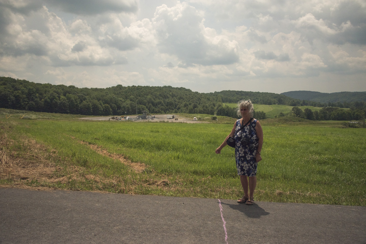 """Vera Scroggins stands by a line on the road in Susquehanna County where an injunction by Cabot Oil and Gas restricts her physical movement, 2015.                                                                                                                                                                                                                                                                                                    /* Style Definitions */  table.MsoNormalTable {mso-style-name:""""Table Normal""""; mso-tstyle-rowband-size:0; mso-tstyle-colband-size:0; mso-style-noshow:yes; mso-style-priority:99; mso-style-parent:""""""""; mso-padding-alt:0in 5.4pt 0in 5.4pt; mso-para-margin-top:0in; mso-para-margin-right:0in; mso-para-margin-bottom:10.0pt; mso-para-margin-left:0in; line-height:115%; mso-pagination:widow-orphan; font-size:11.0pt; font-family:""""Times New Roman"""",""""serif""""; mso-ascii-font-family:""""Times New Roman""""; mso-ascii-theme-font:minor-latin; mso-hansi-font-family:""""Times New Roman""""; mso-hansi-theme-font:minor-latin; mso-bidi-font-family:""""Times New Roman""""; mso-bidi-theme-font:minor-bidi;}    © Nina Berman/MSDP 2015"""