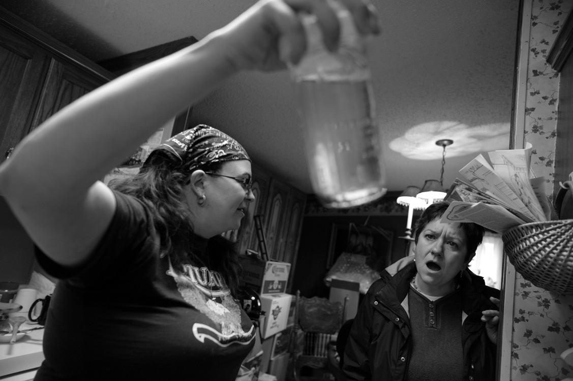 "Kim McEvoy shows Carrie Hahn the contaminated water that the DEP has proclaimed ""safe"" to drink after Rex Energy began gas exploration in their area outside Evans City. Both women became activists out of frustration and anger when, they felt, both local and state authorities turned their back ion their plight.  ©   Lynn Johnson/MSDP 2012"