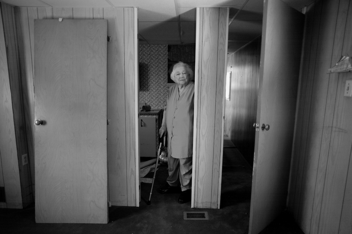 Betty Whyte stands in her now empty mobile home in Riverdale Trailer Park. The land underneath was sold to Aqua America as the site for a water extraction plant. Residents, many of whom were elderly and living on restricted budgets, were forced to move suddenly and with only $1,200 to $2,500 in compensation. Betty and her husband, Bill, have been married for fifty-one years. This was their home for much of that time.  ©   Lynn Johnson/MSDP 2012