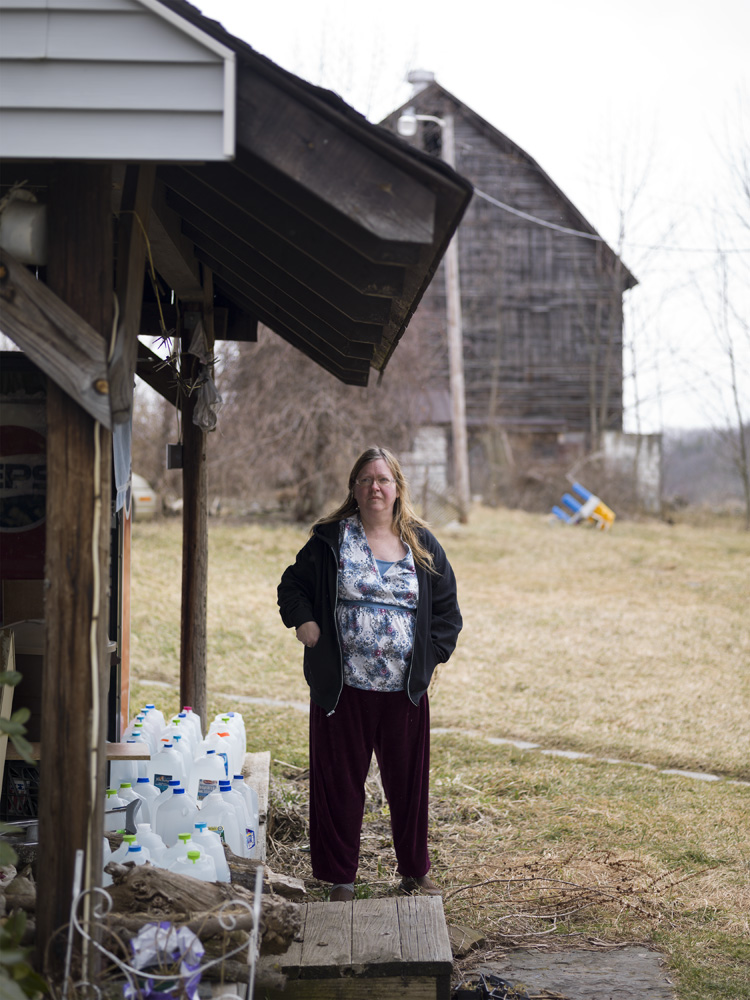 Pat Farnelli, outside her home that has lost most of its value after her well water went bad. She claims her well was contaminated by nearby Cabot Oil and Gas gas-drilling activities. Dimock, Susquehanna County, 2012.  ©   Nina Berman/MSDP 2012