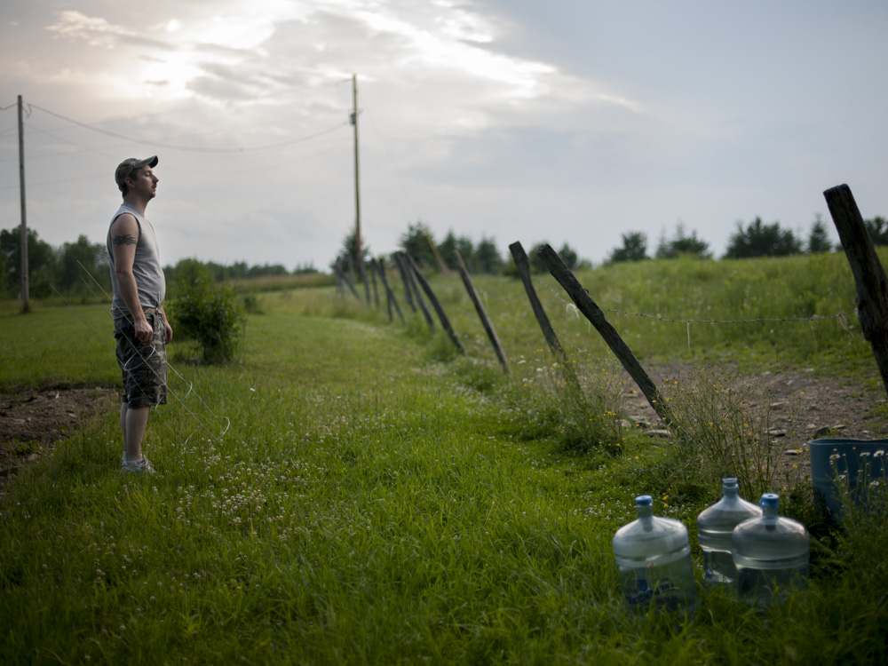 Jason Lamphere looks out over his property. He and his family have been without well water since 2010 after methane migrated into their system. A garden plot behind him lays unplanted since he lacks clean water to irrigate it. He believes nearby gas drilling and fracking caused the problem. Monroeton, Bradford County, 2011.  ©   Nina Berman/MSDP 2011