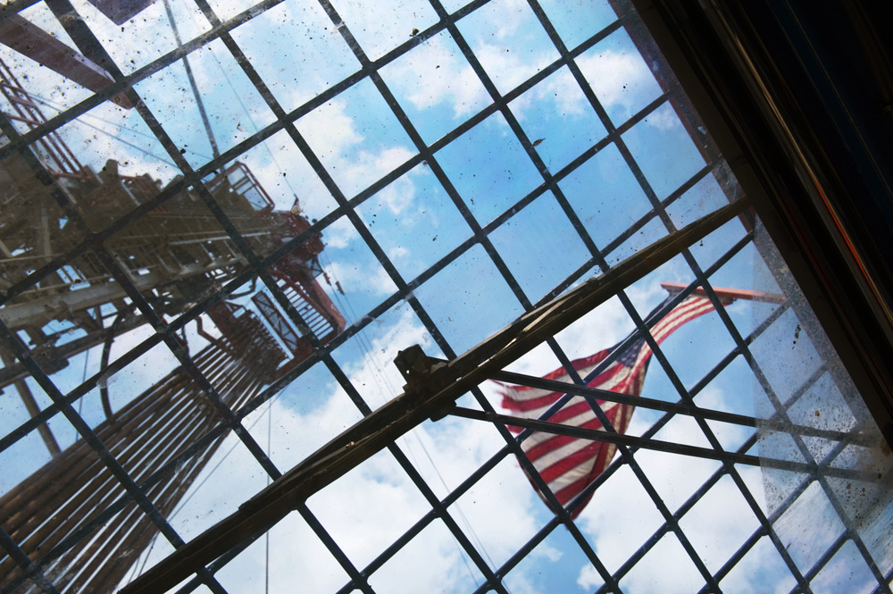 Looking up at a natural-gas drilling rig in Washington County, PA, through a ceiling window of the control room on the drilling platform. The flag is used to help the people working on the rig determine which way the wind is blowing, to help avoid airborne contaminates when present. ©Scott Goldsmith/MSDP 2012