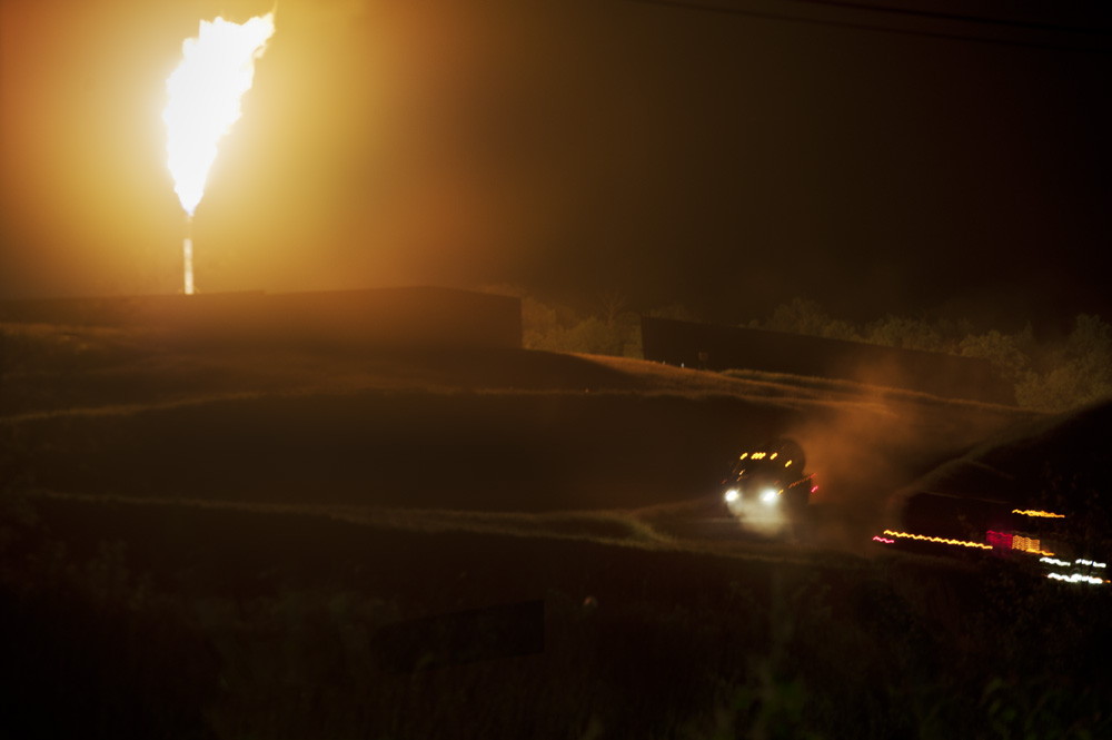 A gas flare at night, industry traffic in the foreground. © Scott Goldsmith/MSDP 2012