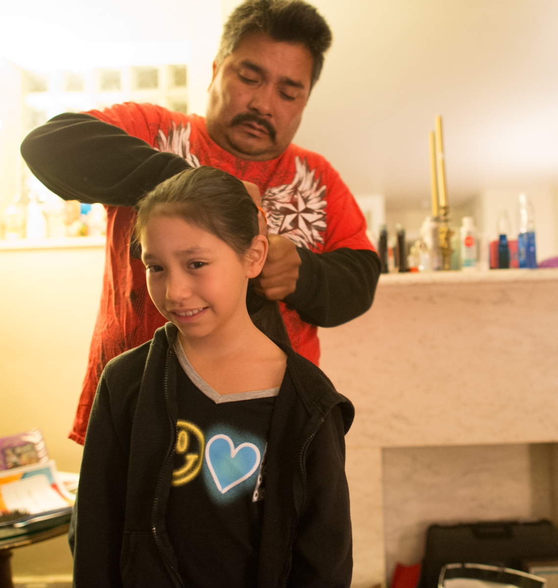 Jose helps Emma with her hair before she heads off to school.  © Nate Guidry/TDW 2017