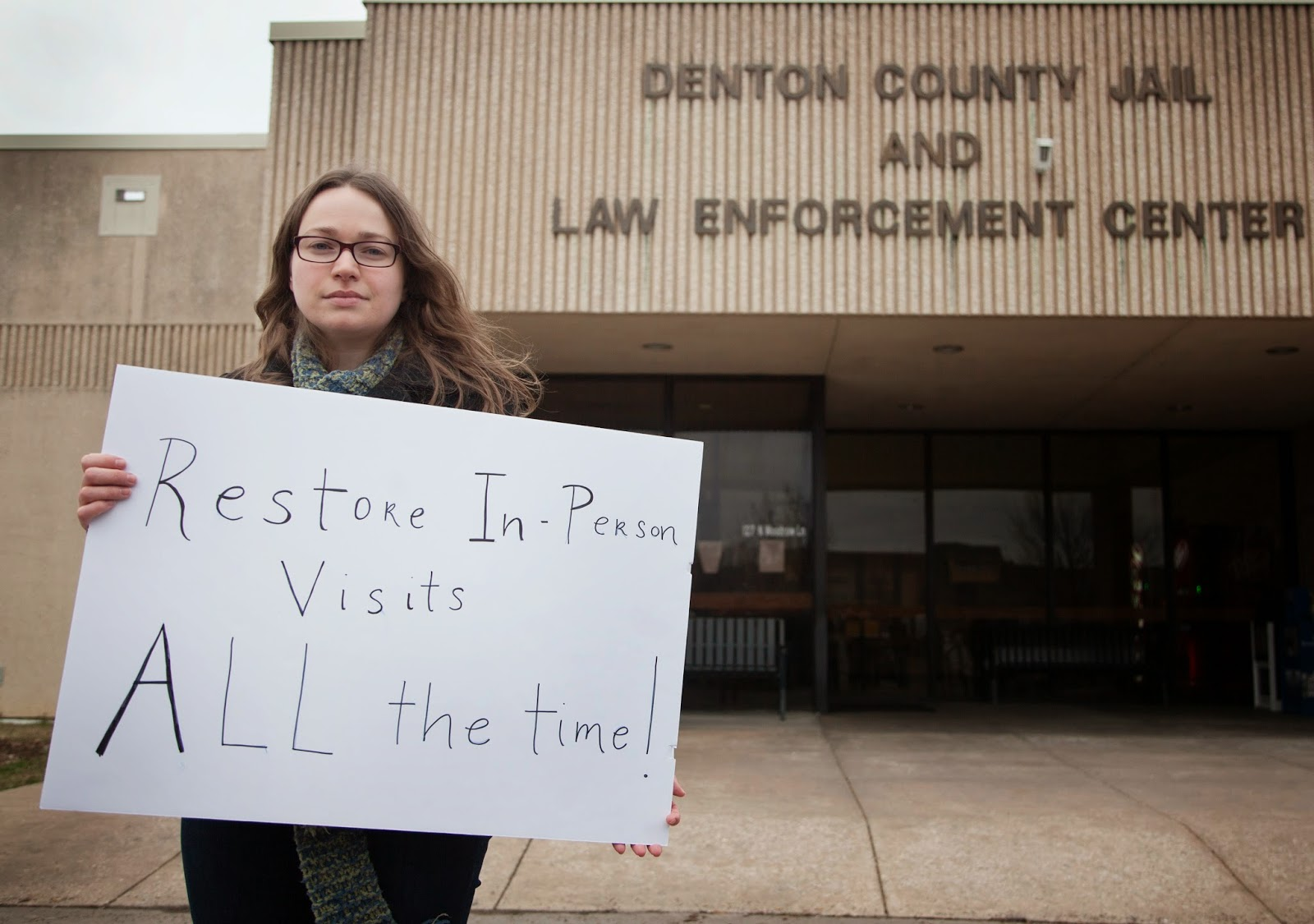 """Jennifer Long posed with a sign that reads, """"Restore in-person visits all the time!"""" in front of the Denton County Jail where protesters gathered Feb. 26, 2015, to protest the jail's video visitation system.  Photo by Kristen Watson for the Denton Record-Chronicle."""
