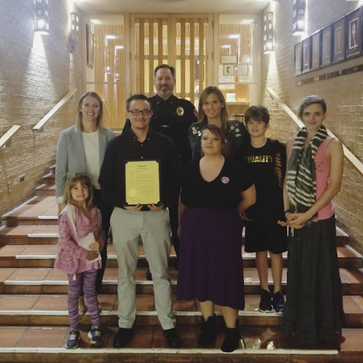 Daniel Bryant-Gawne is pictured holding the proclamation with Denton LGBTQ liaisons Sara Kuechler (leftmost) and Chris Summit (third from left), activist Amber Briggle (on Summit's left).