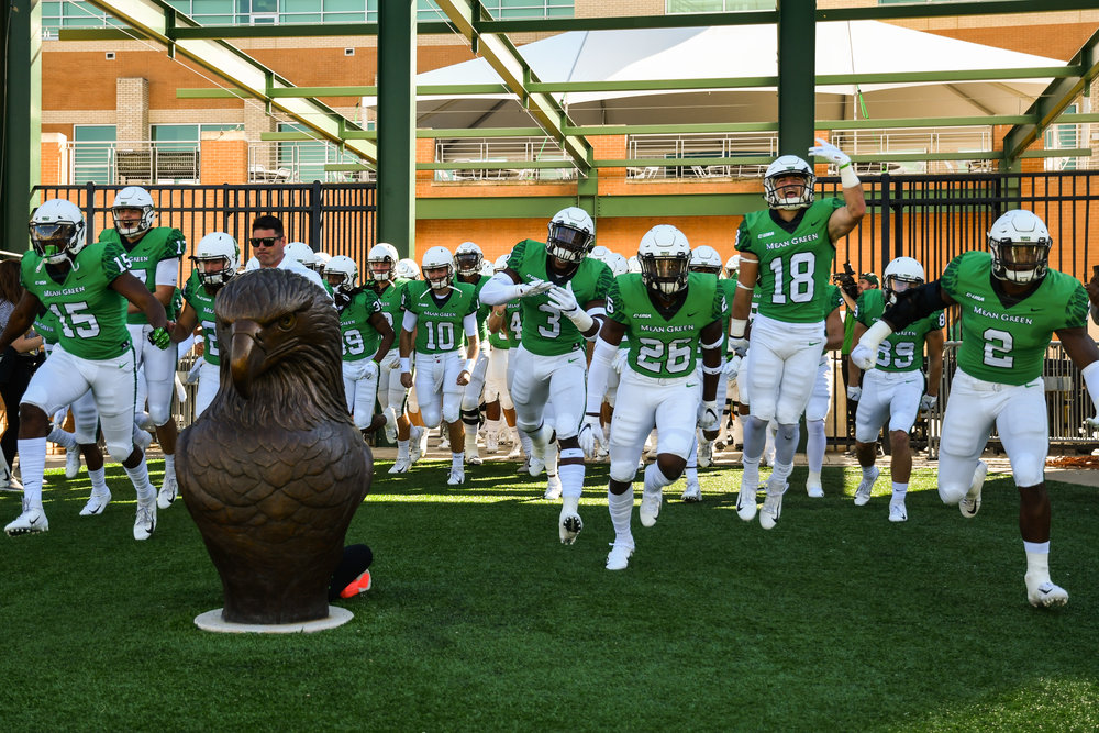 UNT Football players running onto the field by a statue of an eagle before a game started. Photo by Samuel Gomez.
