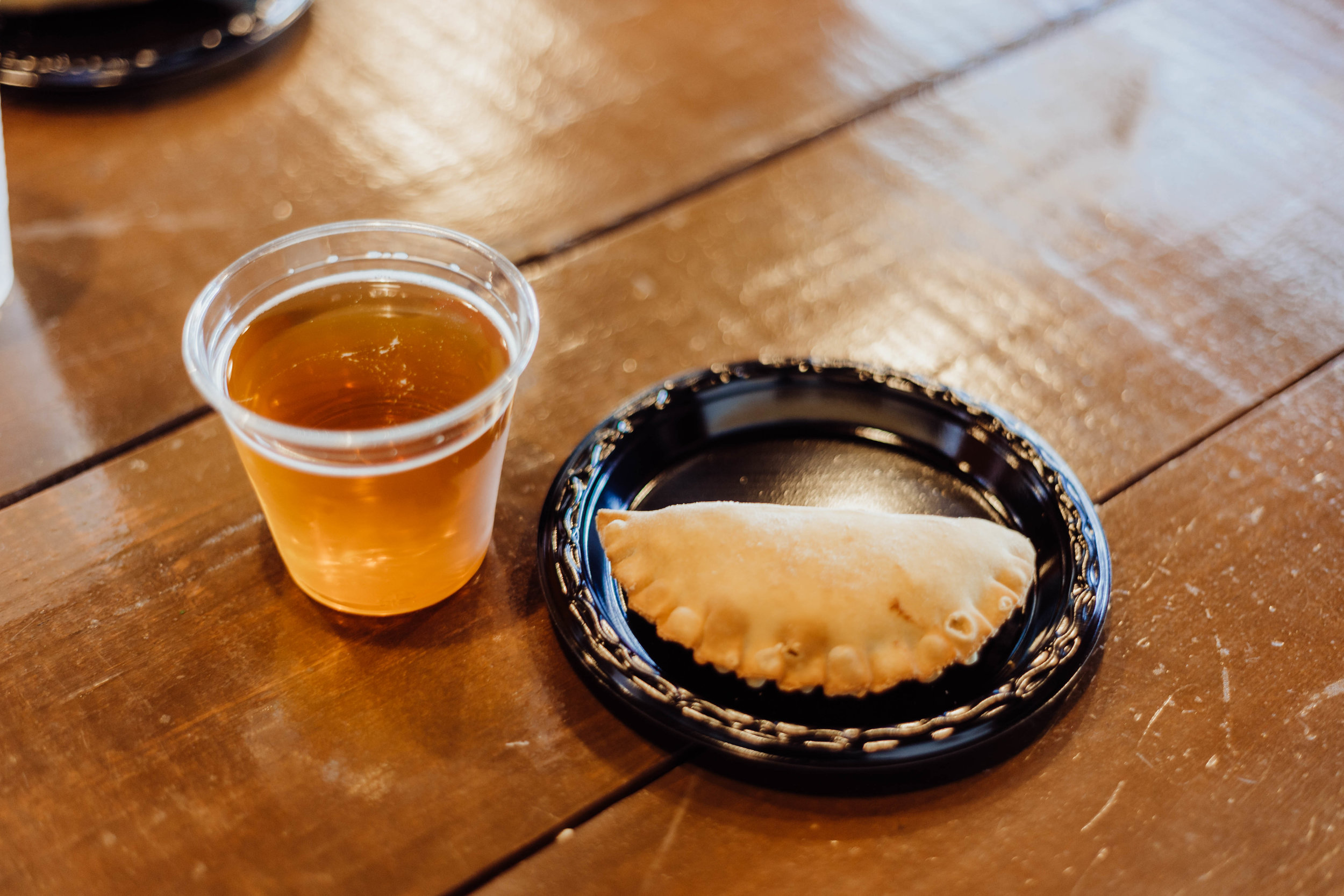 The fourth course, featuring a Sausage, Onion and Potato Empanada with Smoked Habanero Cheese and the Greenbelt Farmhouse Ale. Photo by Jennifer Meza.