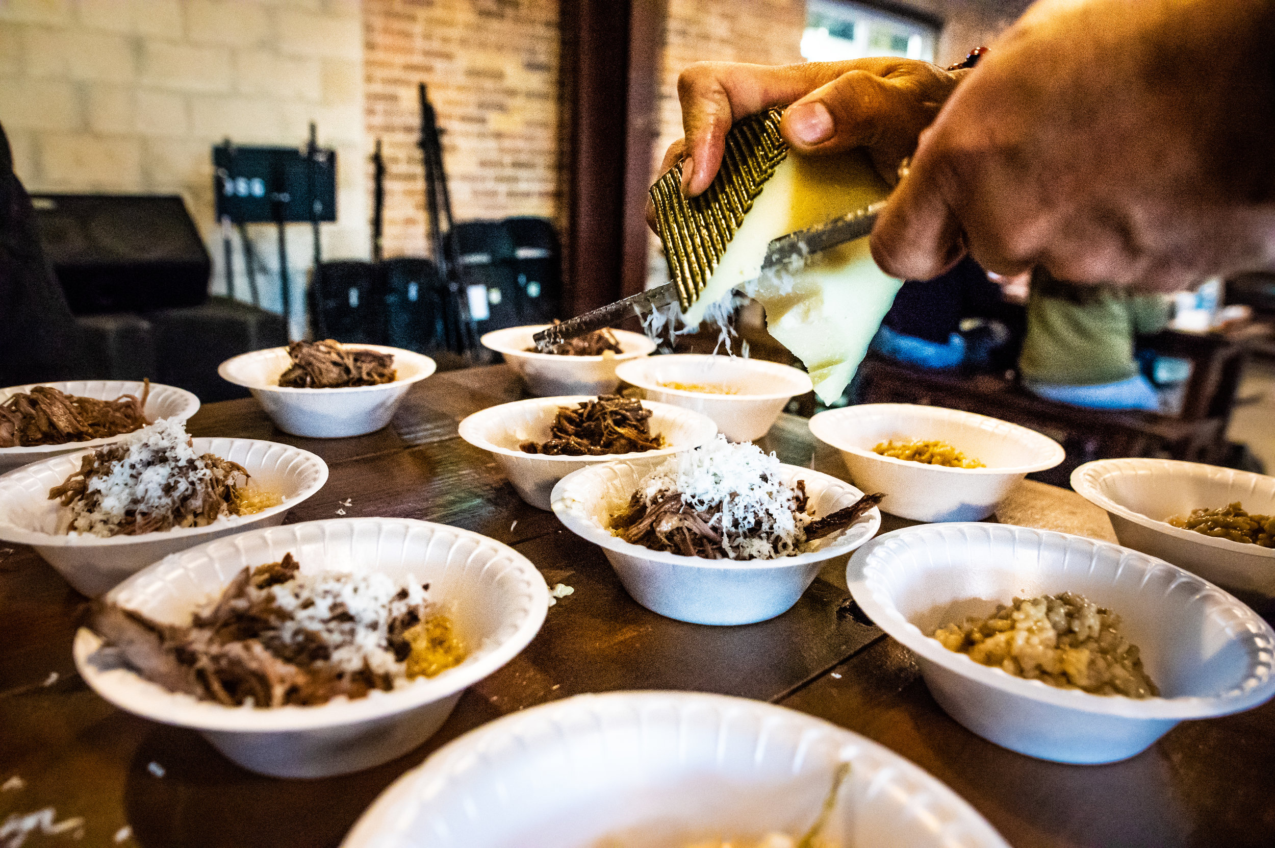 The kitchen staff in action, topping the fifth course - Red Wine Braised Brisket Risotto - with some of Ten:One's Campo de Montalban. Photo by Garrett Smith.