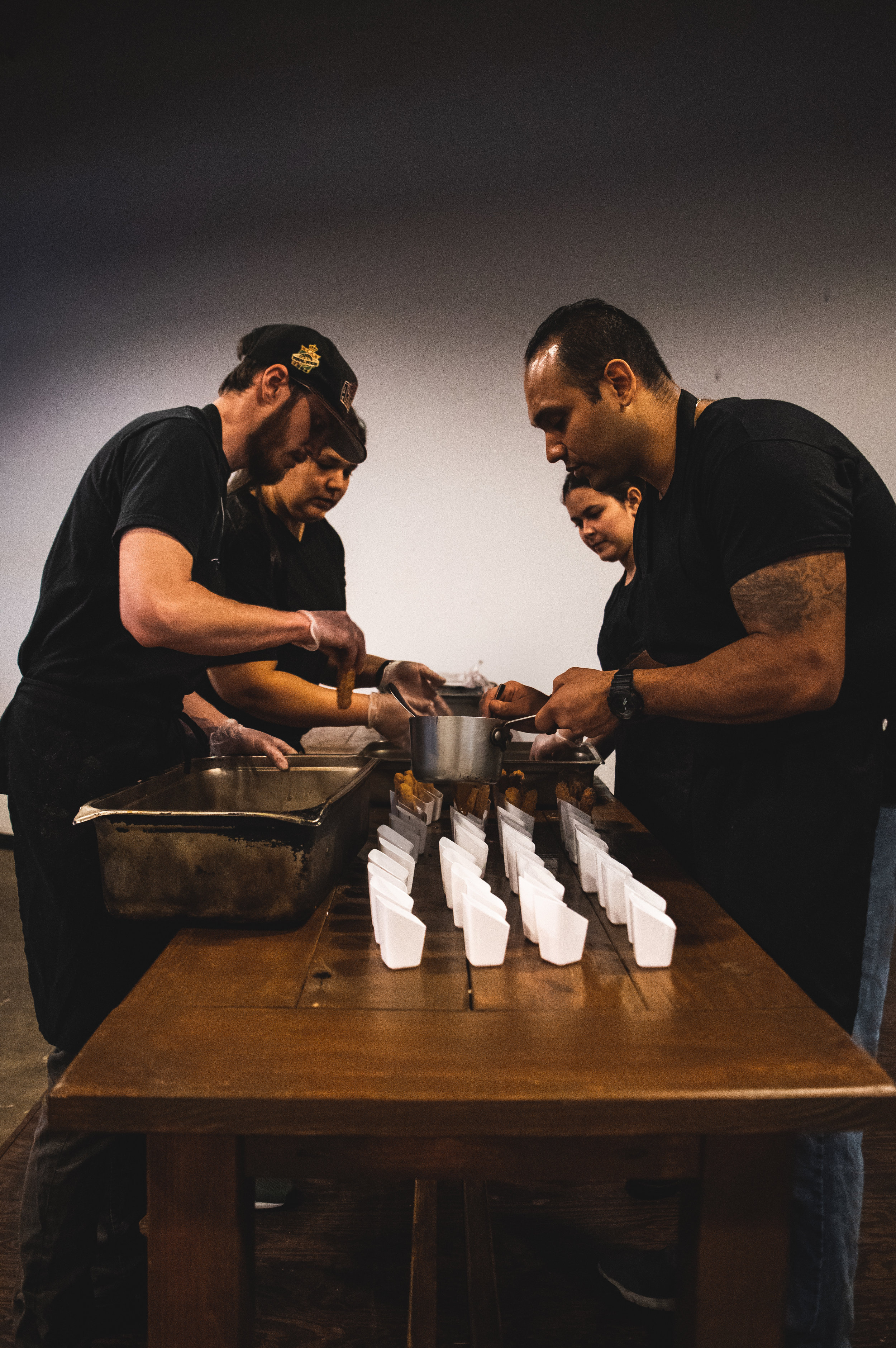 The kitchen staff working to portion the sauces in the final dessert course. Photo by Garrett Smith.