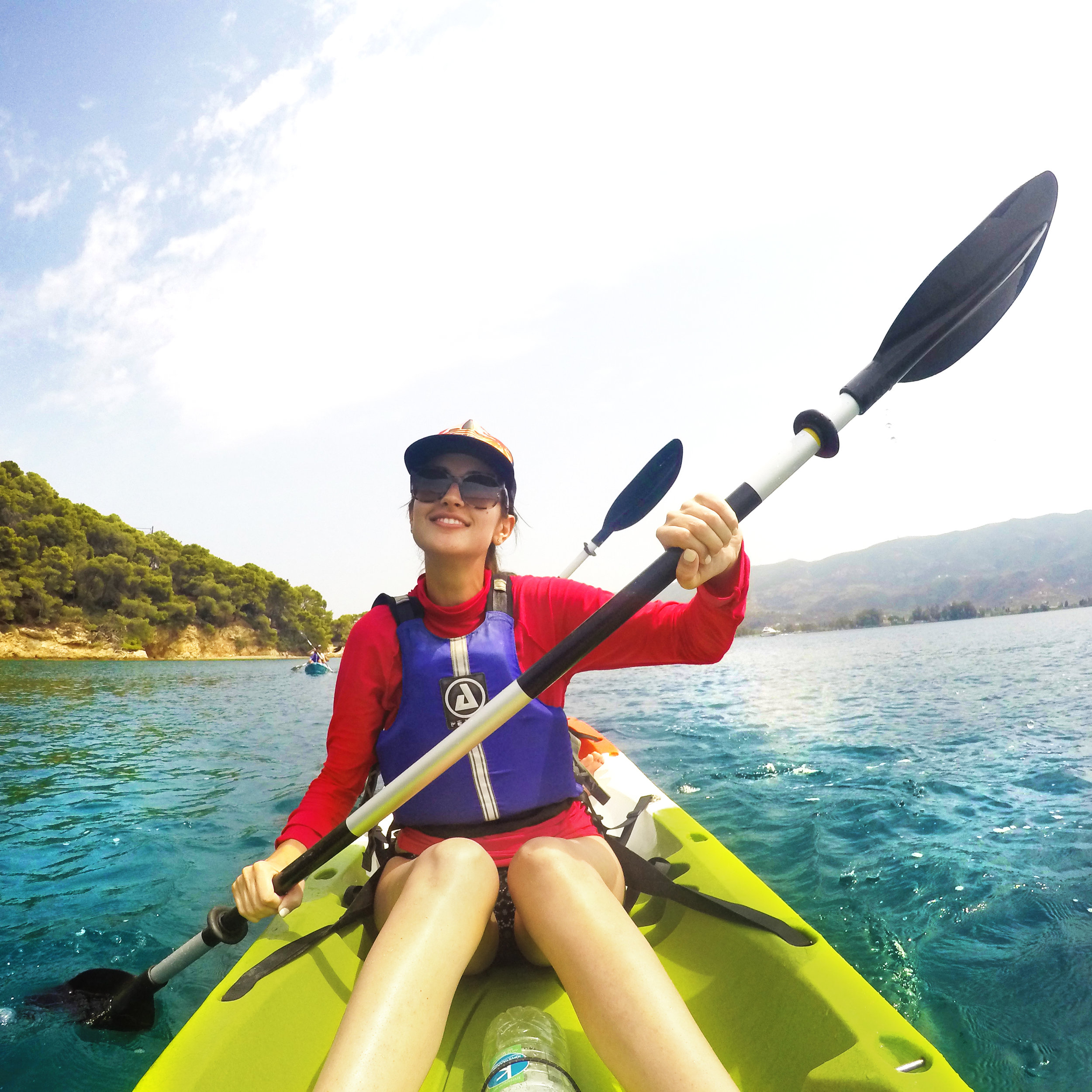 A HellaTravels solo female traveler kayaks in Greece on of our Greece Tours.