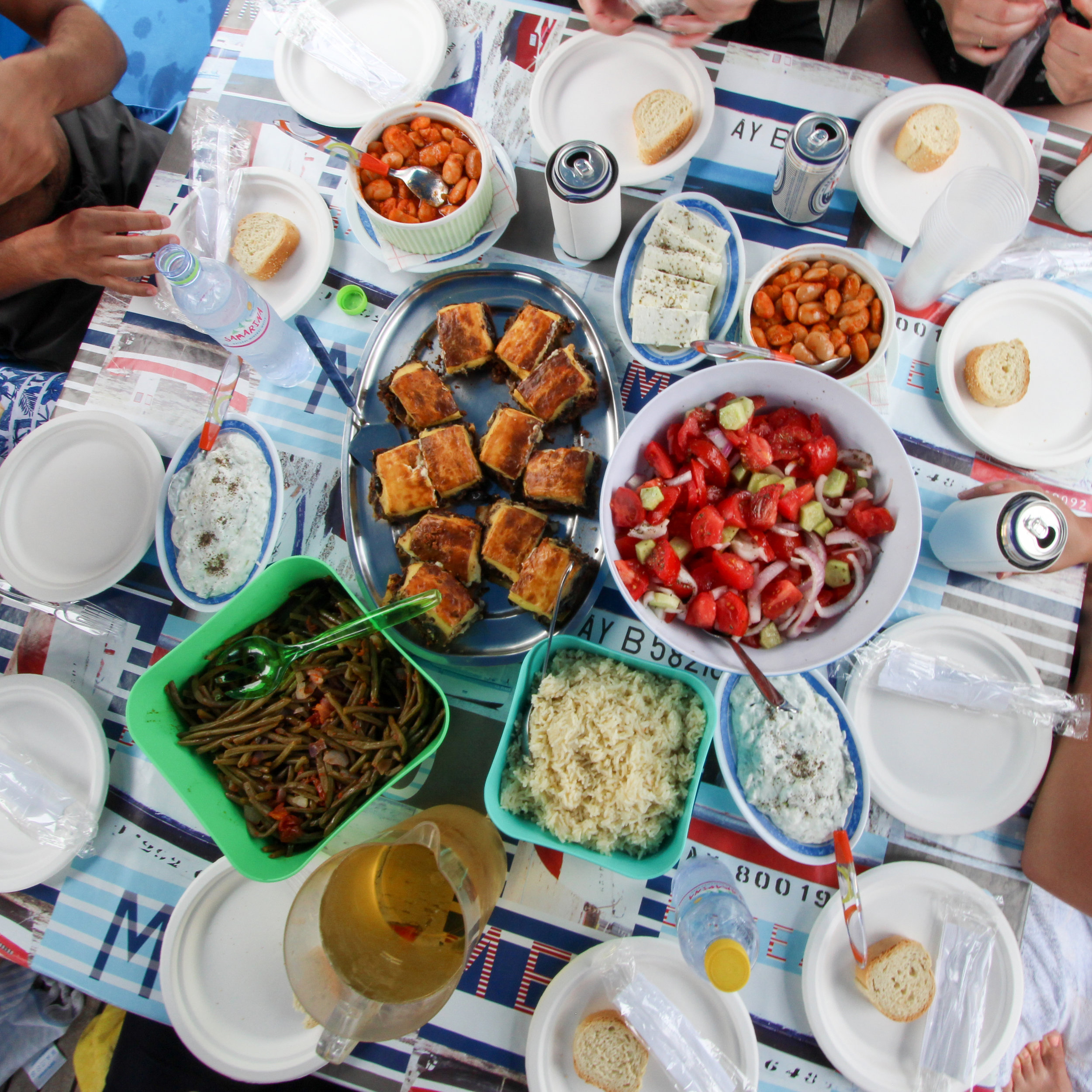 HellaTravels solo female travelers gather around delicious Greek food on a sailing excursion on a HellaTravels Greece Vacation.