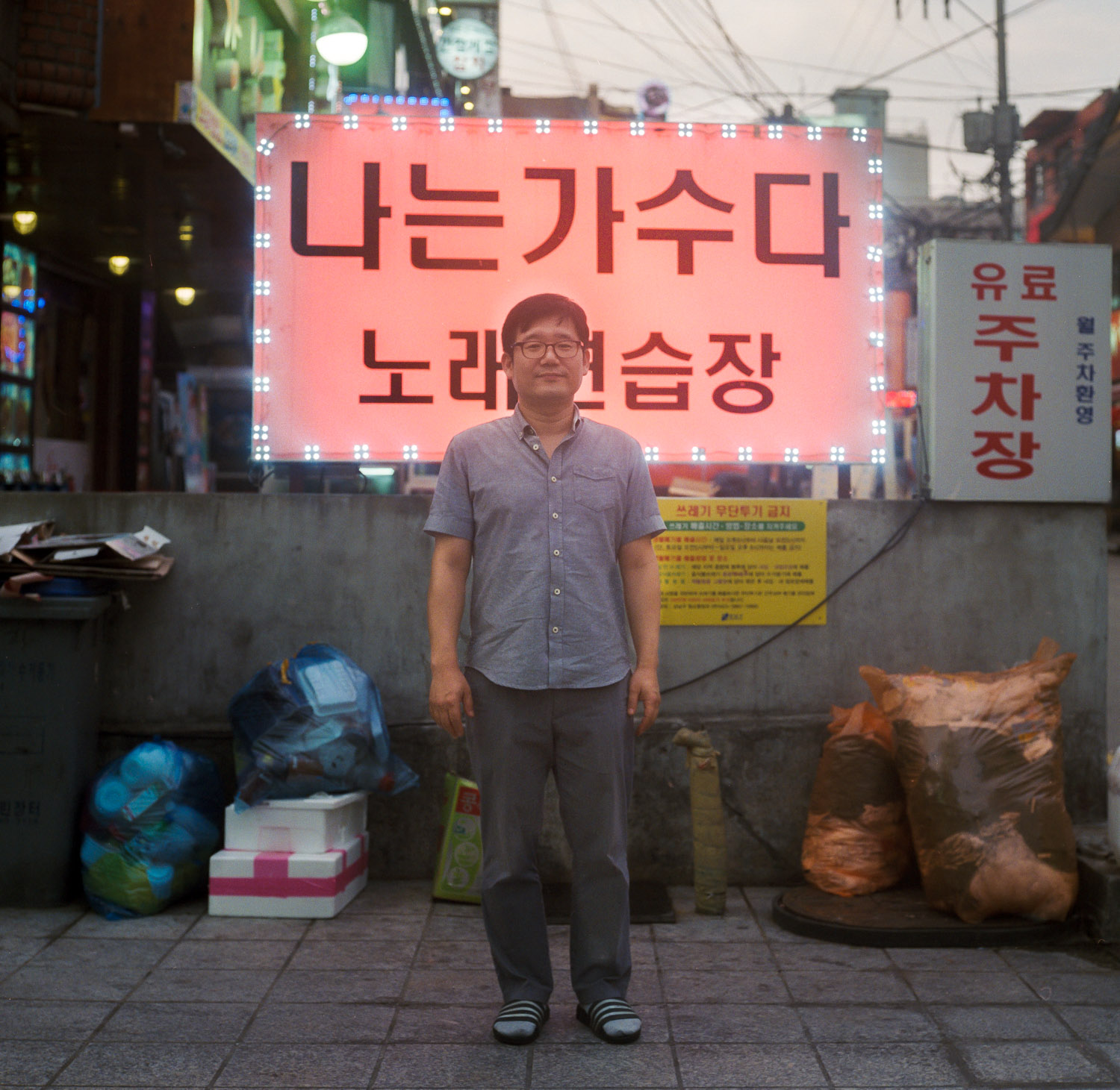""" I want to be singer "" . An entertainment game room owner standing in front of a Karaoke Room advertising in Gangnam district / Seoul"