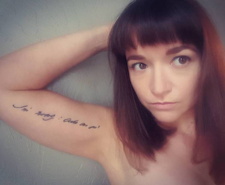 "Photo of Jessica Morey-Collins with a line of Dickinson's handwriting tattooed on her arm. It reads, ""I'm Nobody! Who are you?"""