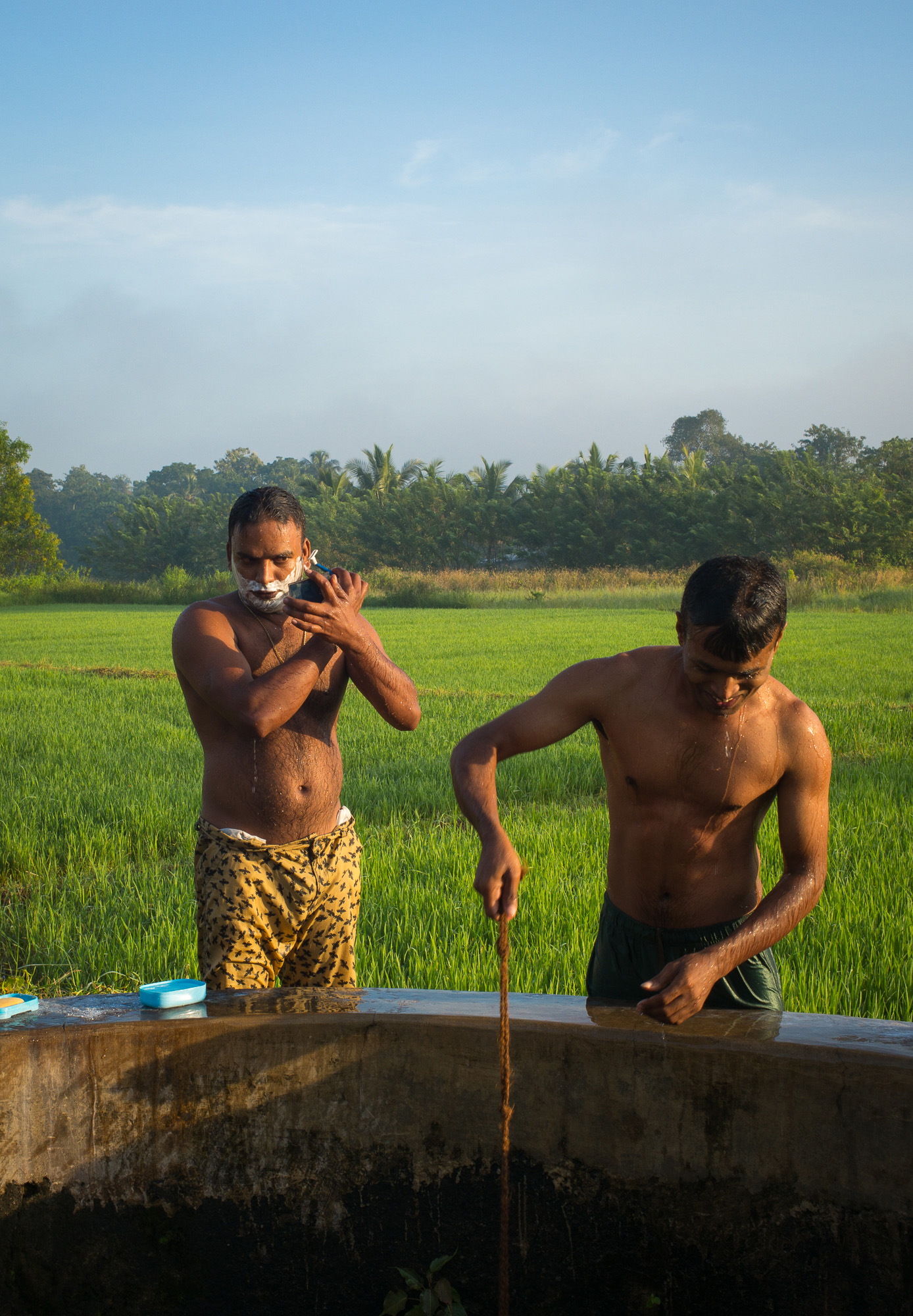 Men bathing in the morning light, Kurunegala, North Western Province