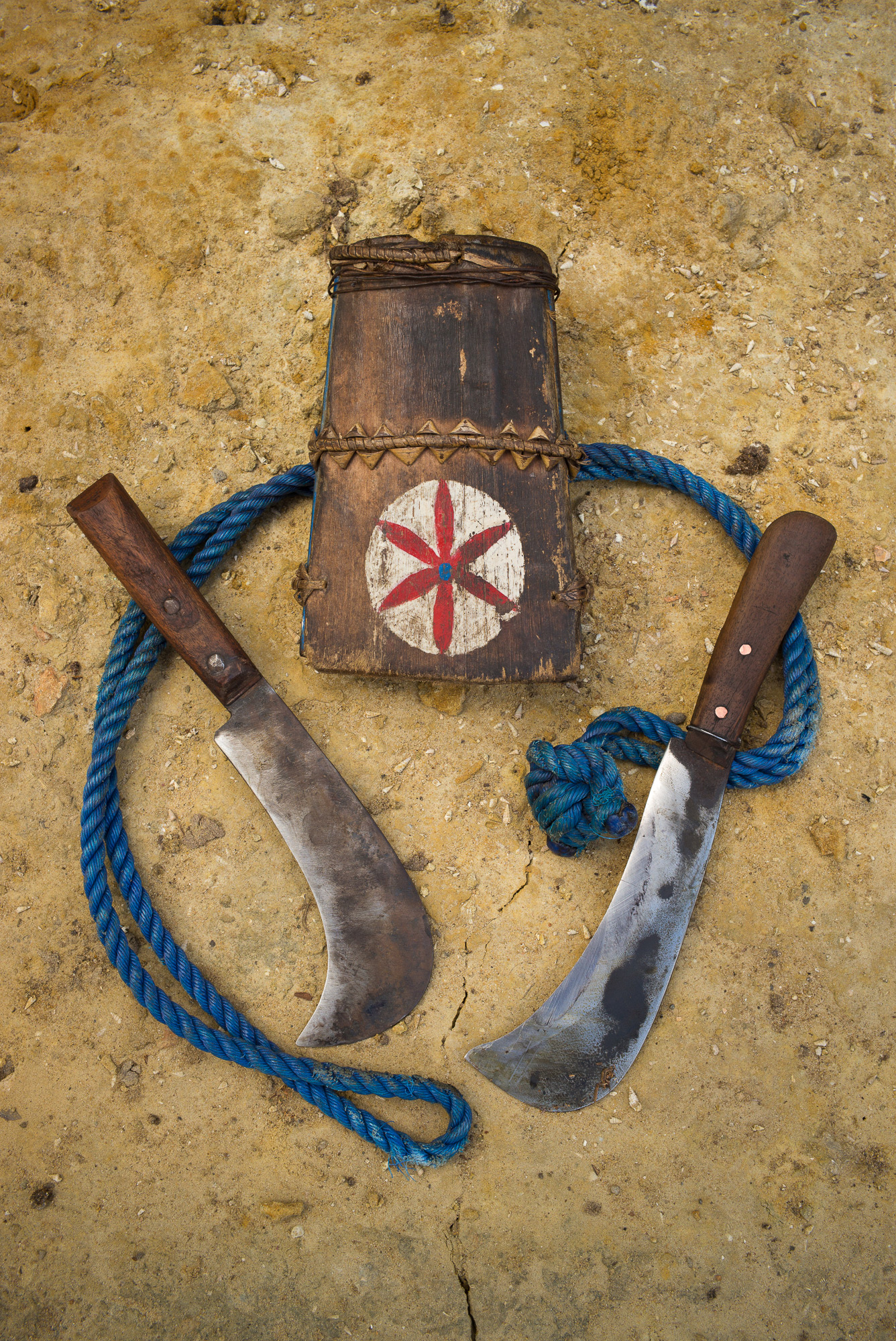 Tools of the trade: the knives used to trim the  sapathe  and the leaves, and the rope with which they secure themselves to the tree while they work.