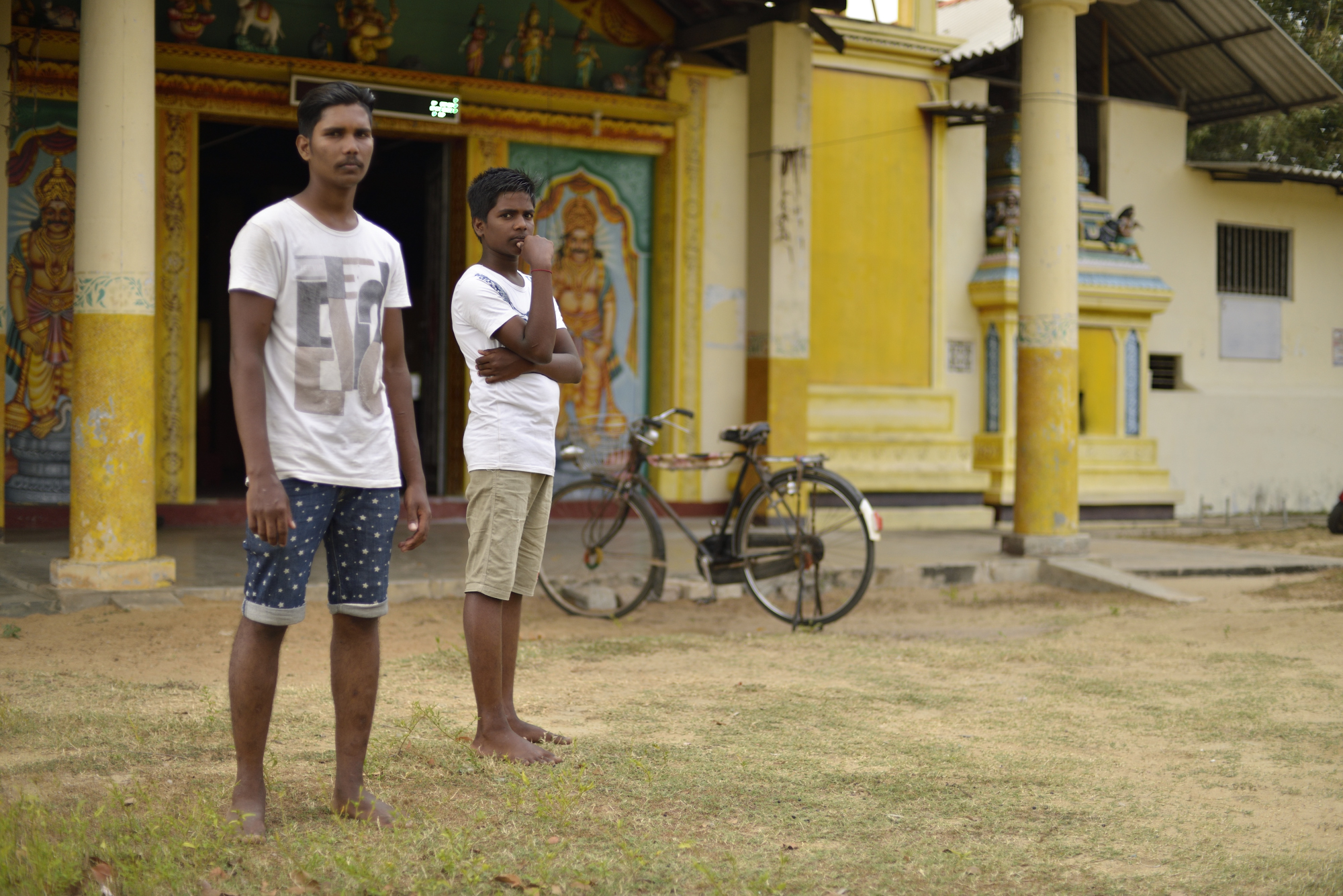 """Nirosan and his younger brother Tanusan outside the village temple, which they cannot enter because of the """"unclean"""" status of the Nalavar caste. Nirosan, from a family of tappers,works as a cook: """"If people there knew what my family does for work, it would be a problem… I cannot say."""""""