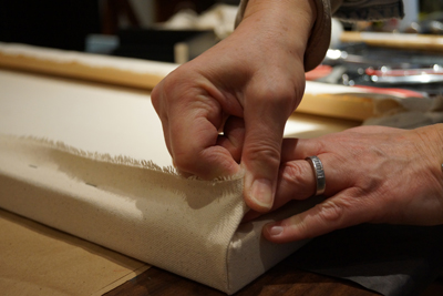 Tightly pulling the corners and wrapping them so they are flat.