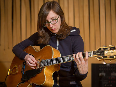 """One of improvised music's most in-demand guitarists, Mary Halvorson has been active in New York since 2002, following jazz studies at Wesleyan University and the New School. Critics have called her """"a singular talent"""" (Lloyd Sachs, JazzTimes ), """"NYC's least-predictable improviser"""" (Howard Mandel, City Arts ), """"one of the most exciting and original guitarists in jazz—or otherwise"""" (Steve Dollar, Wall Street Journal ), and """"one of today's most formidable bandleaders"""" (Francis Davis, Village Voice ). The  Philadelphia City Paper's Shaun Brady adds, """"Halvorson has been steadily reshaping the sound of jazz guitar in recent years with her elastic, sometimes-fluid, sometimes-shredding, wholly unique style.""""  After three years of study with visionary composer and saxophonist Anthony Braxton, Ms. Halvorson became an active member of several of his bands, including his trio, septet and 12+1tet. To date, she appears on over ten of Mr. Braxton's recordings. Ms. Halvorson has also performed alongside iconic guitarist Marc Ribot, in his bands Sun Ship and The Young Philadelphians, and with the bassist Trevor Dunn in his Trio-Convulsant. Over the past decade she has worked with such diverse bandleaders as Tim Berne, Taylor Ho Bynum, Tomas Fujiwara, Ingrid Laubrock, Jason Moran, Joe Morris, Tom Rainey, Tomeka Reid and John Zorn.  As a bandleader and composer, one of Ms. Halvorson's primary outlets is her longstanding trio, featuring bassist John Hébert and drummer Ches Smith. Since their 2008 debut album, Dragon's Head , the band was recognized as a rising star jazz band by  Downbeat Magazine for five consecutive years. Most recently she has formed an octet, adding trumpeter Jonathan Finlayson, saxophonists Jon Irabagon and Ingrid Laubrock, trombonist Jacob Garchik, and pedal steel guitarist Susan Alcorn. Their debut 2016 release, Away With You , on the Firehouse 12 Record label, was called """"radiant"""" by the  New York Times and """"one of the most intricate and entrancing sets of her c"""