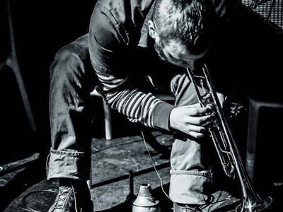 """Nate Wooley was born in 1974 in Clatskanie, Oregon, a town of 2,000 people in the timber country of the Pacific Northwestern corner of the U.S. He began playing trumpet professionally with his father, a big band saxophonist, at the age of 13. His time in Oregon, a place of relative quiet and slow time reference, instilled in Nate a musical aesthetic that has informed all of his music making for the past 20 years, but in no situation more than his solo trumpet performances.  Nate moved to New York in 2001, and has since become one of the most in-demand trumpet players in the burgeoning Brooklyn jazz, improv, noise, and new music scenes. He has performed regularly with such icons as John Zorn, Anthony Braxton, Eliane Radigue, Ken Vandermark, Fred Frith, Evan Parker, and Yoshi Wada, as well as being a collaborator with some of the brightest lights of his generation like Chris Corsano, C. Spencer Yeh, Peter Evans, and Mary Halvorson.  In the past years, Wooley has been gathering international acclaim for his idiosyncratic trumpet language. Time Out New York has called him """"an iconoclastic trumpeter"""". The New York City Jazz Record voted Wooley Musician of the Year 2011 and 2013. An international critics poll in El Intruso Magazine elected him Musician of the Year 2013 and Trumpet Player of the Year for three years in a row. Dave Douglas: """"Nate Wooley is one of the most interesting and unusual trumpet players living today, and that is without hyperbole""""  His work has been featured at the SWR JazzNow stage at Donaueschingen, the WRO Media Arts Biennial in Poland, Kongsberg, North Sea, Music Unlimited, and Copenhagen Jazz Festivals, and the New York New Darmstadt Festivals. In 2011 he was an artist in residence at Issue Project Room in Brooklyn, NY and Cafe Oto in London, England. In 2013 he performed at the Walker Art Center as a featured solo artist.  Nate is the curator of the Database of Recorded American Music ( www.dramonline.org ) and the editor-in-chief of their onl"""