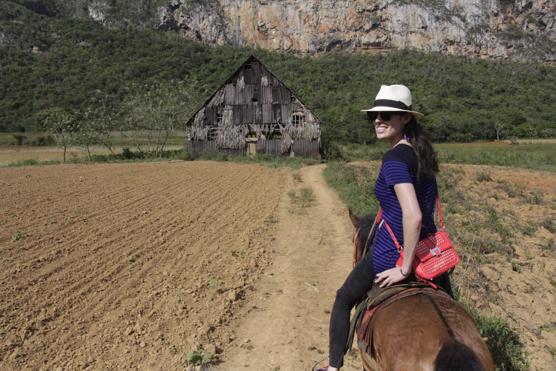 """Emily on horseback is a sight to see. Of course, no one told  Rebecca Minkoff that her purses needed to endure a trot or gallup. Here she is approaching the """"house"""" where farmers dry tobacco leaves."""