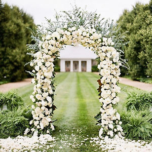 A central wedding arbor adorned with white flowers which will frame a view of the river.