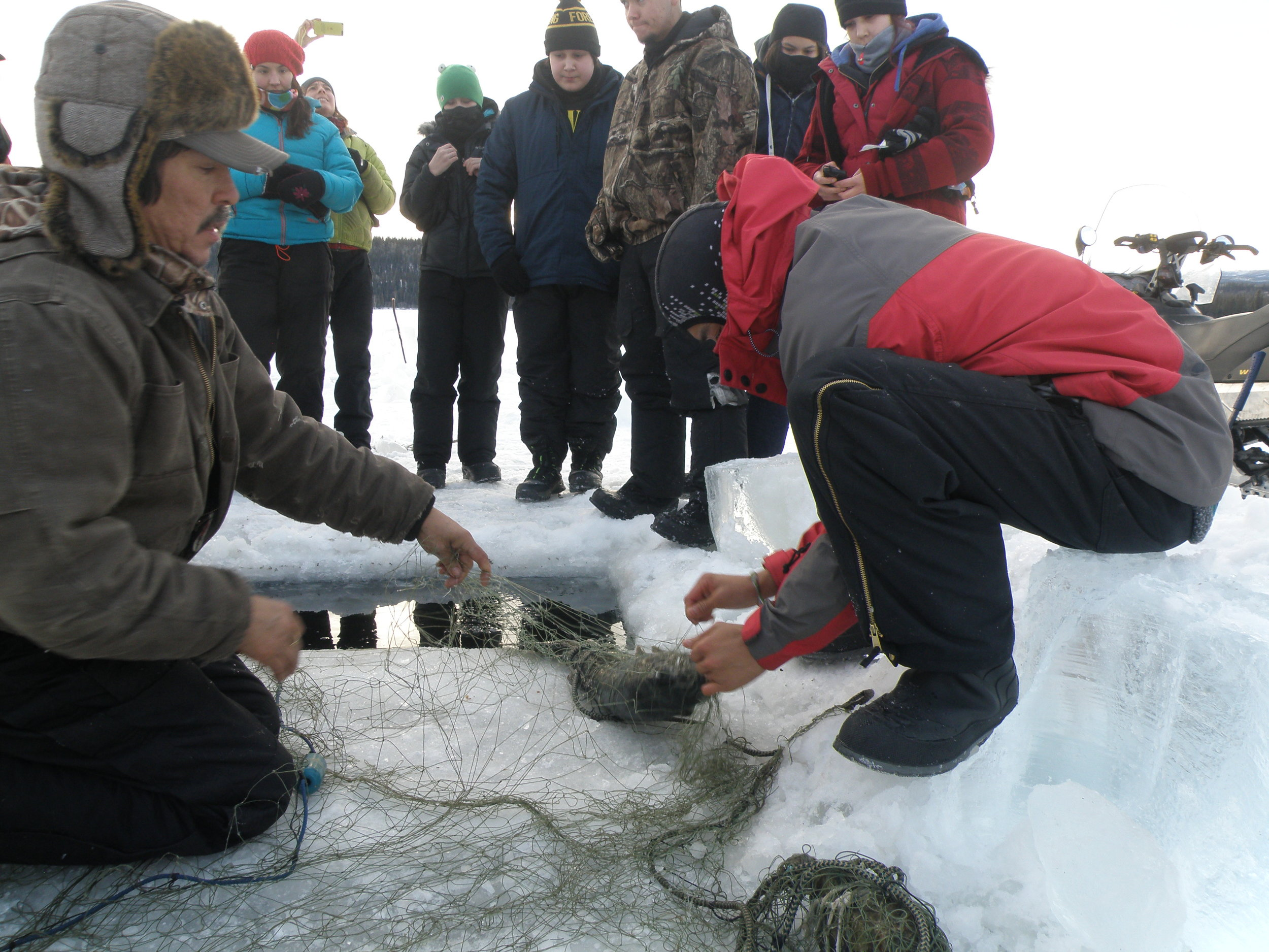 Selkirk First Nation youth learn how to set a net and catch fish under the ice at Winter Fish Camp as part of the  Keeping Our Traditions Project .