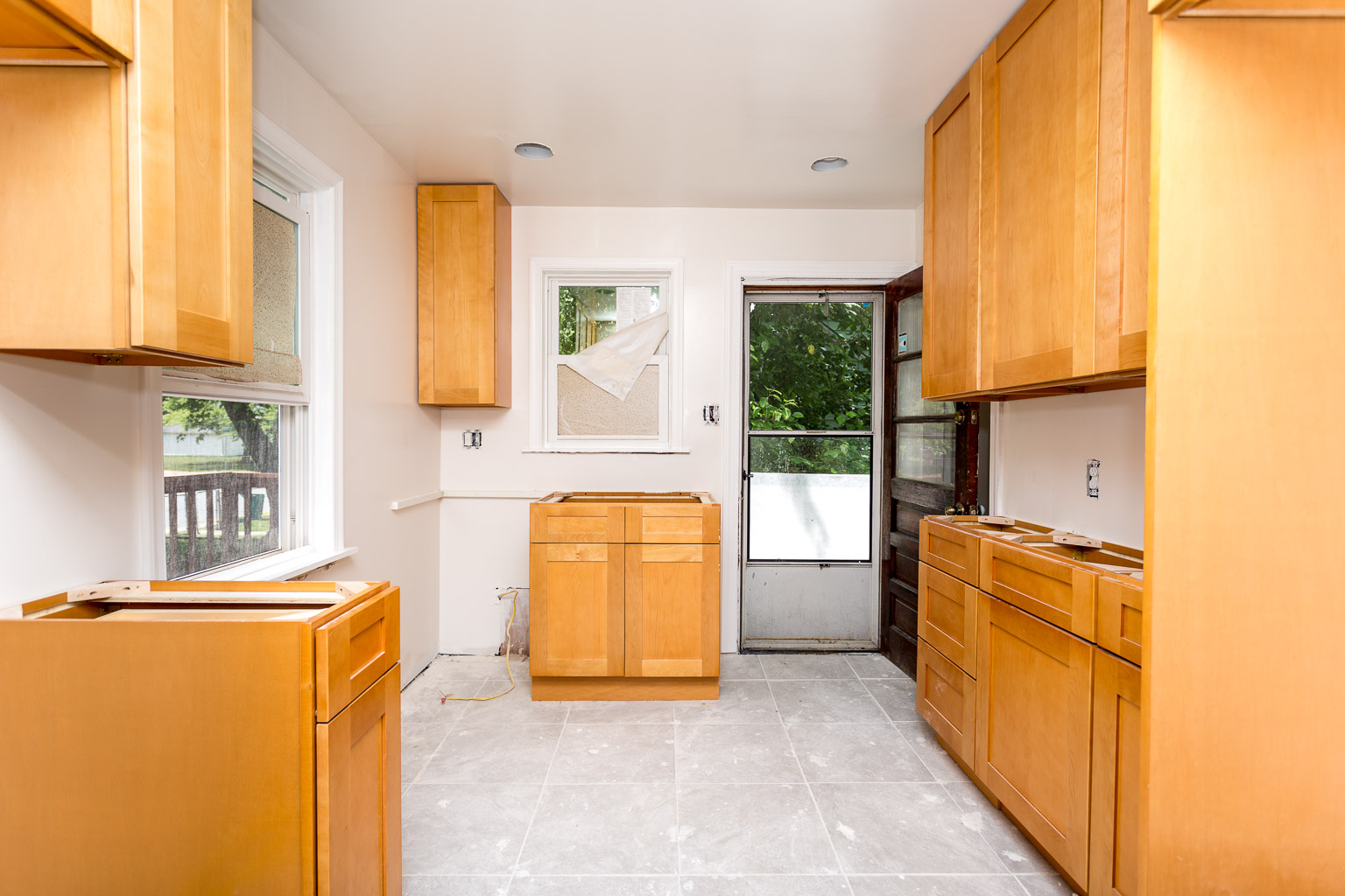 There's recessed lighting now and cabinets that are actually installed properly. The gas line is moved from the right side of the room near the door to the bottom left corner of this photo to create a better flow in the kitchen. All that's left to install is the countertops and the appliances.