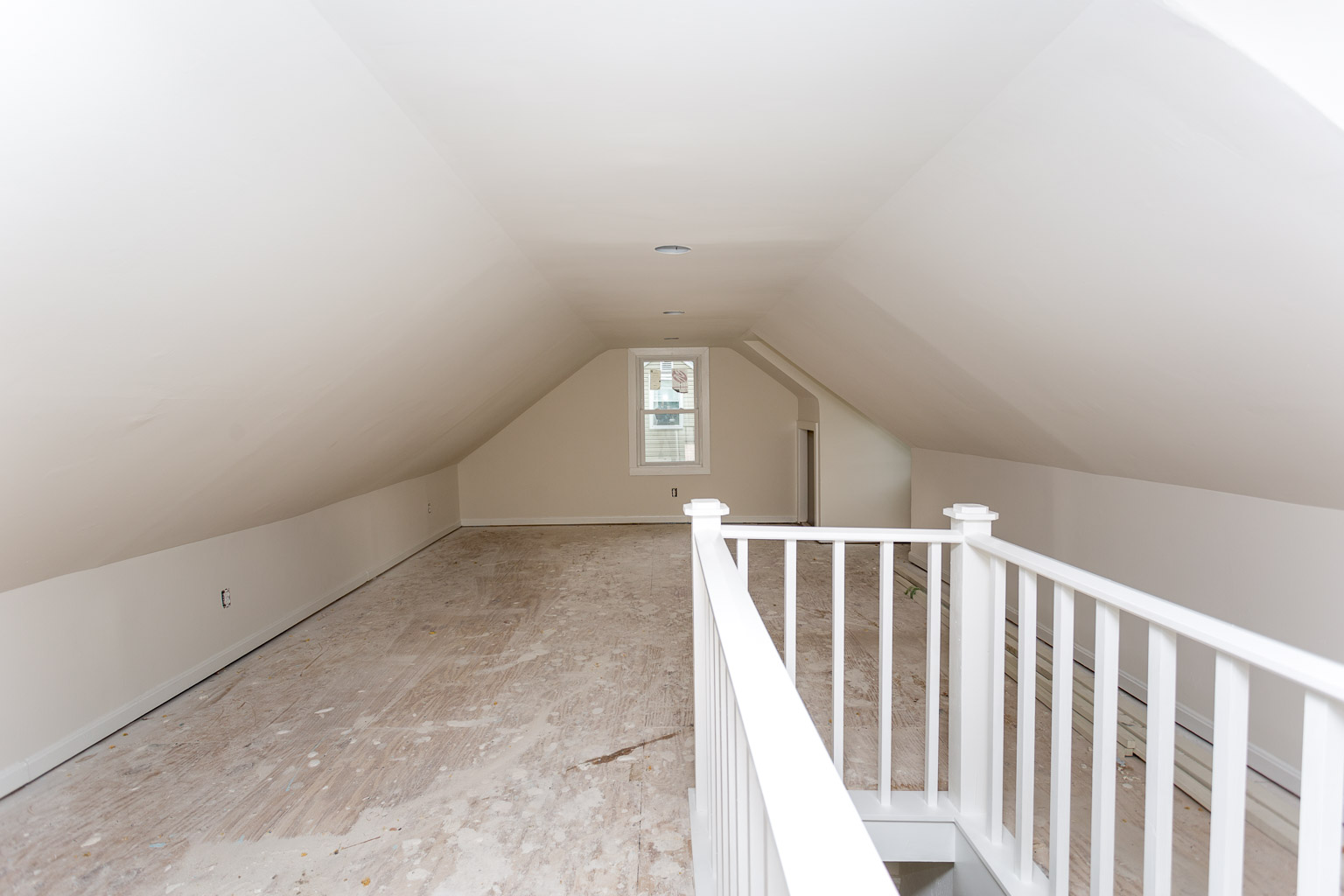 This is the after photo. My new contractor added recessed lighting, replaced the guard rail, repaired the drywall, and primed/painted. All that's left is installing the carpet.