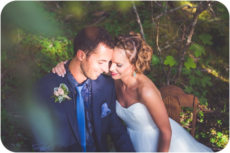 couple snuggling at moss covered table for two after forest elopement