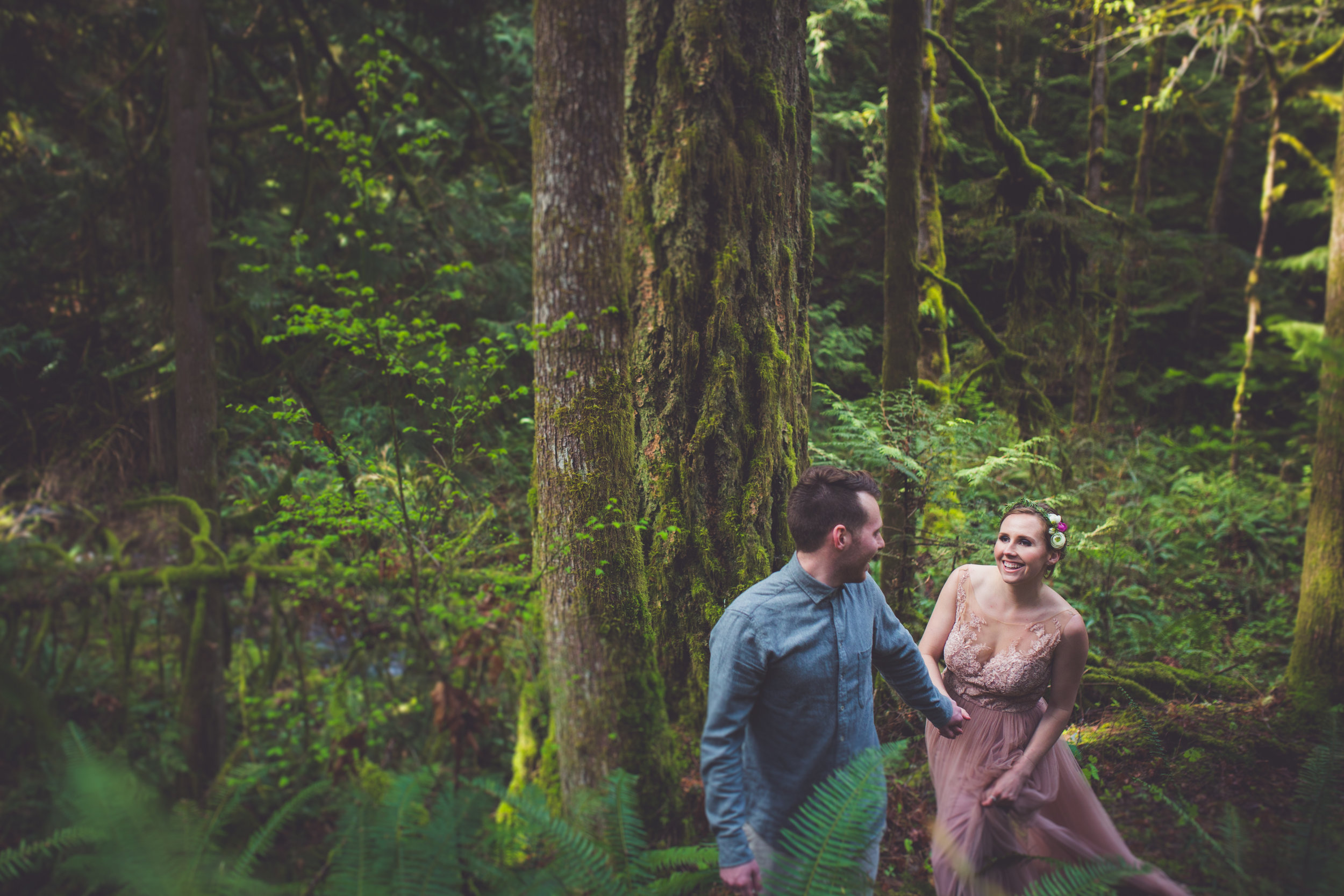 couple running through forest for wedding