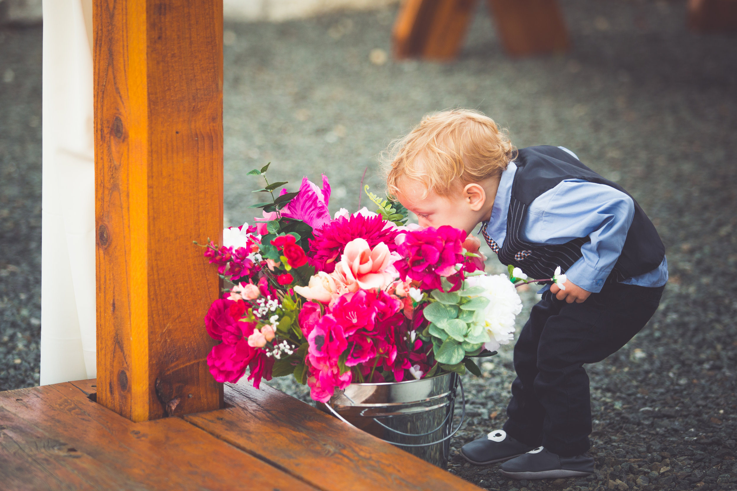 young boy smells wedding flowers