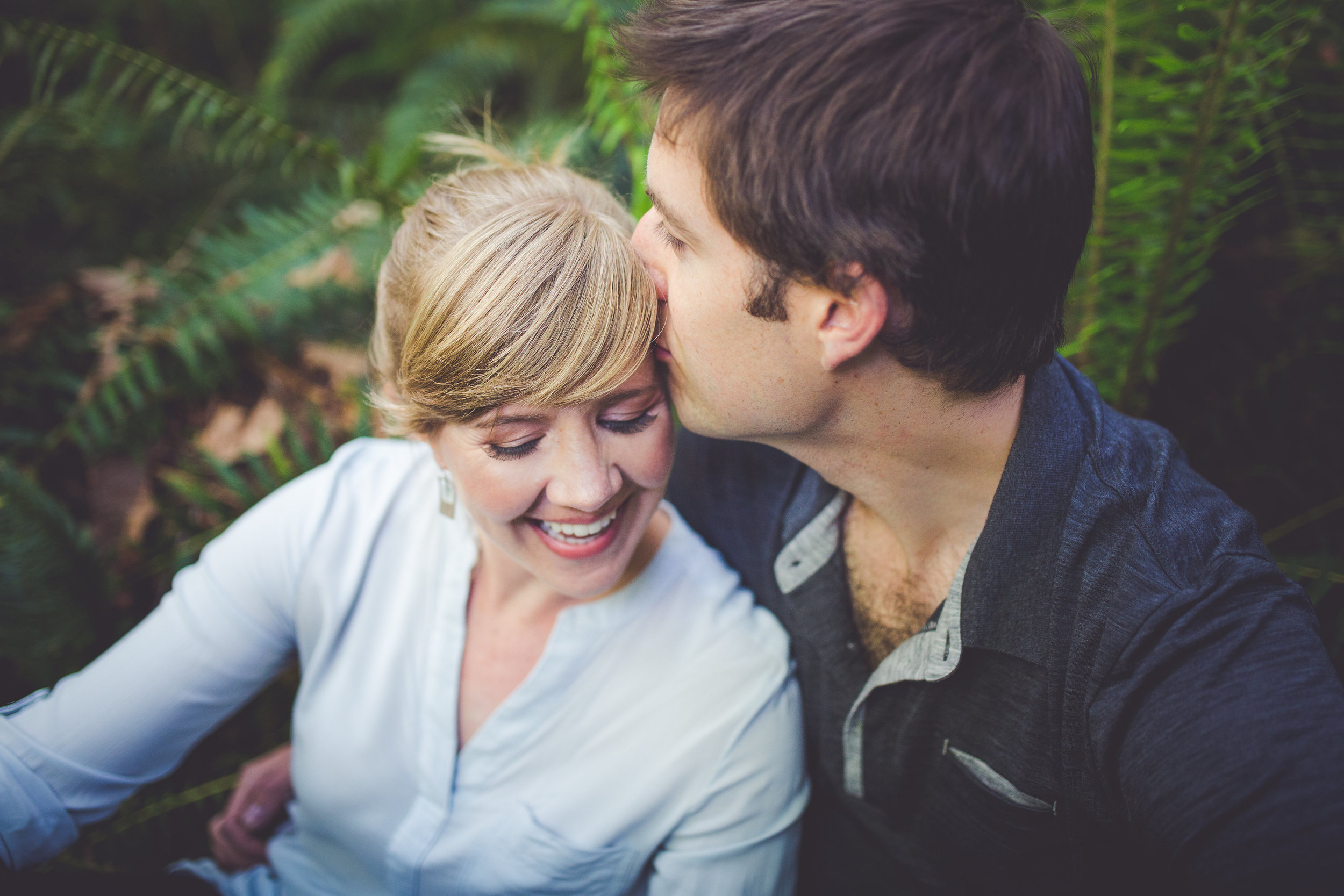 couple in ferns for engagement photos at rosewall creek