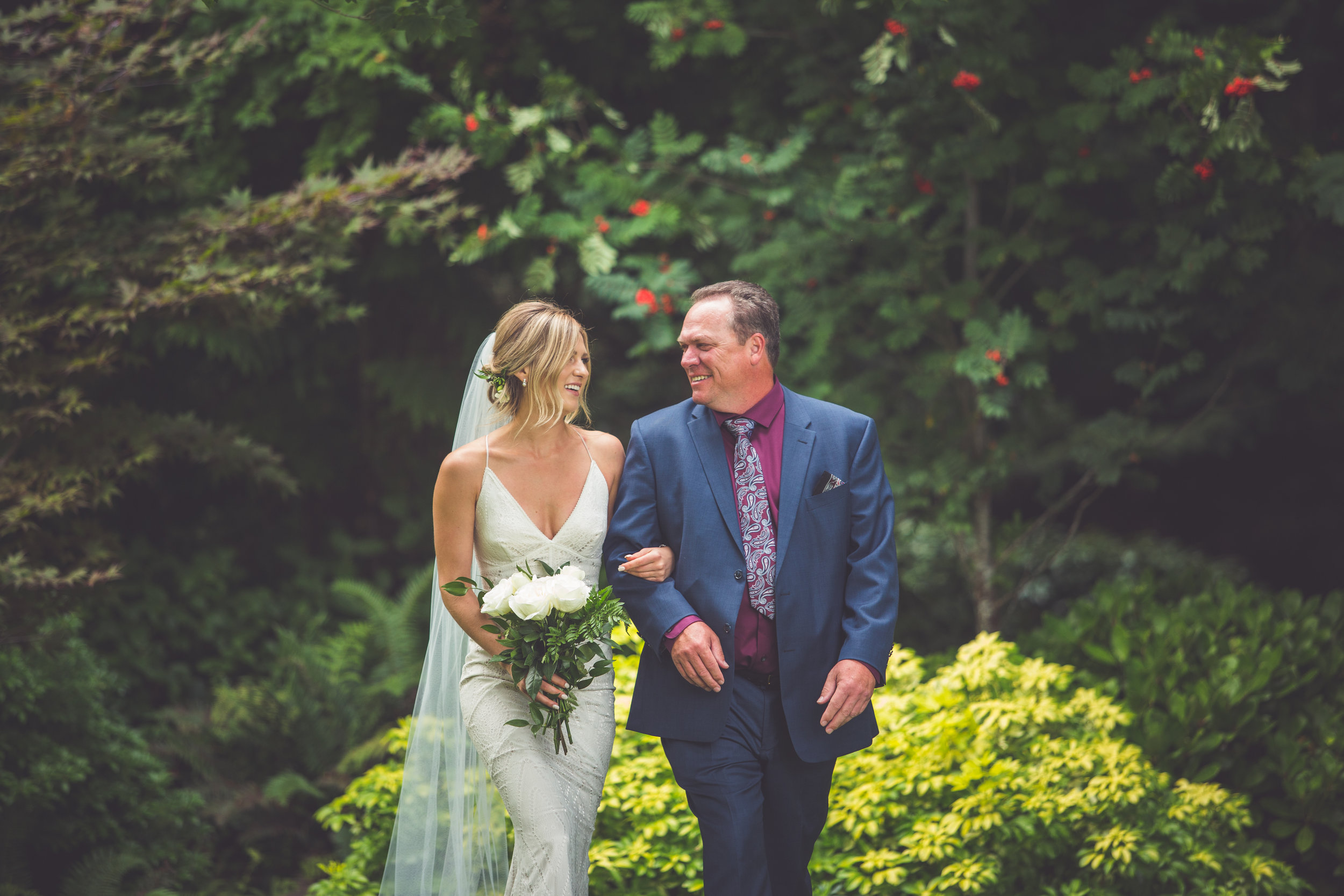 father of the bride walks bride down forested aisle