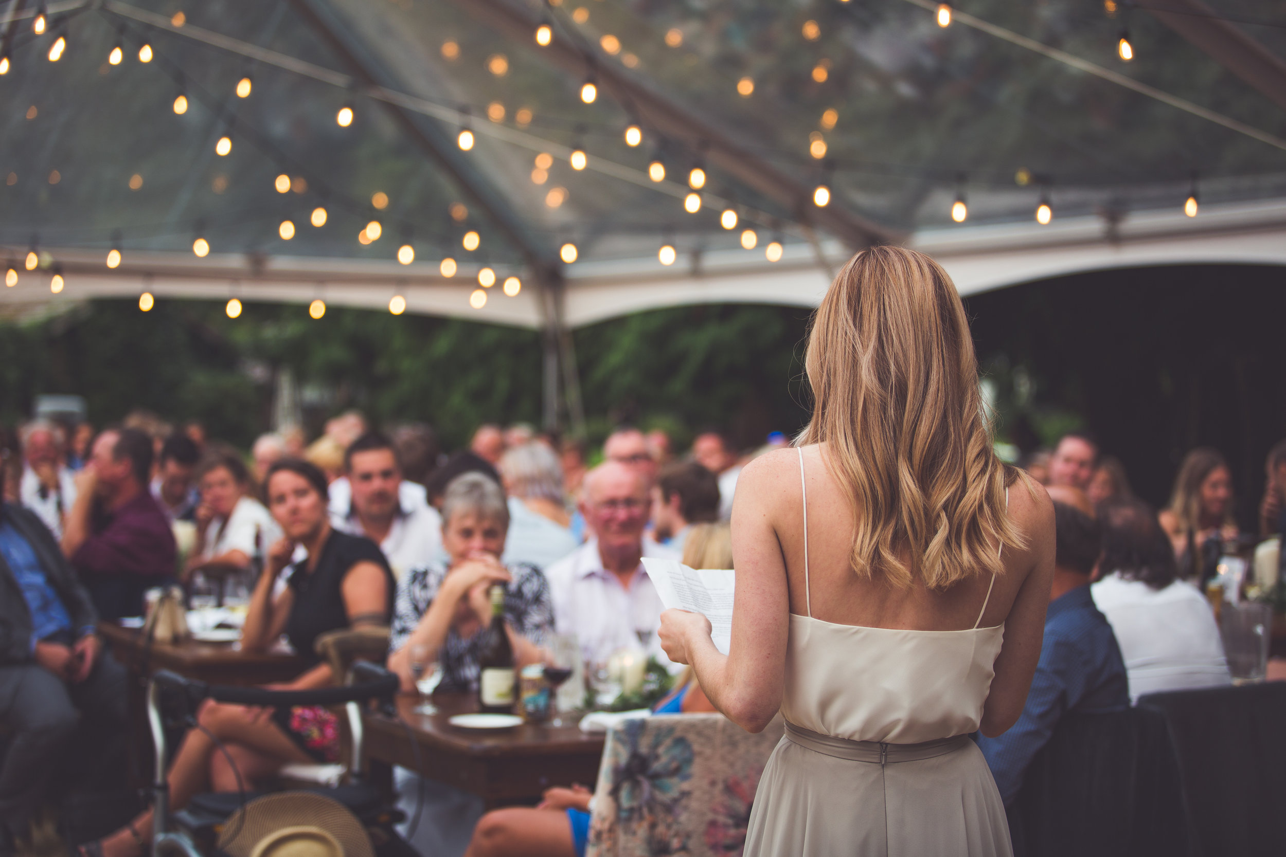 maid of honour gives speech under clear tent with twinkle lights