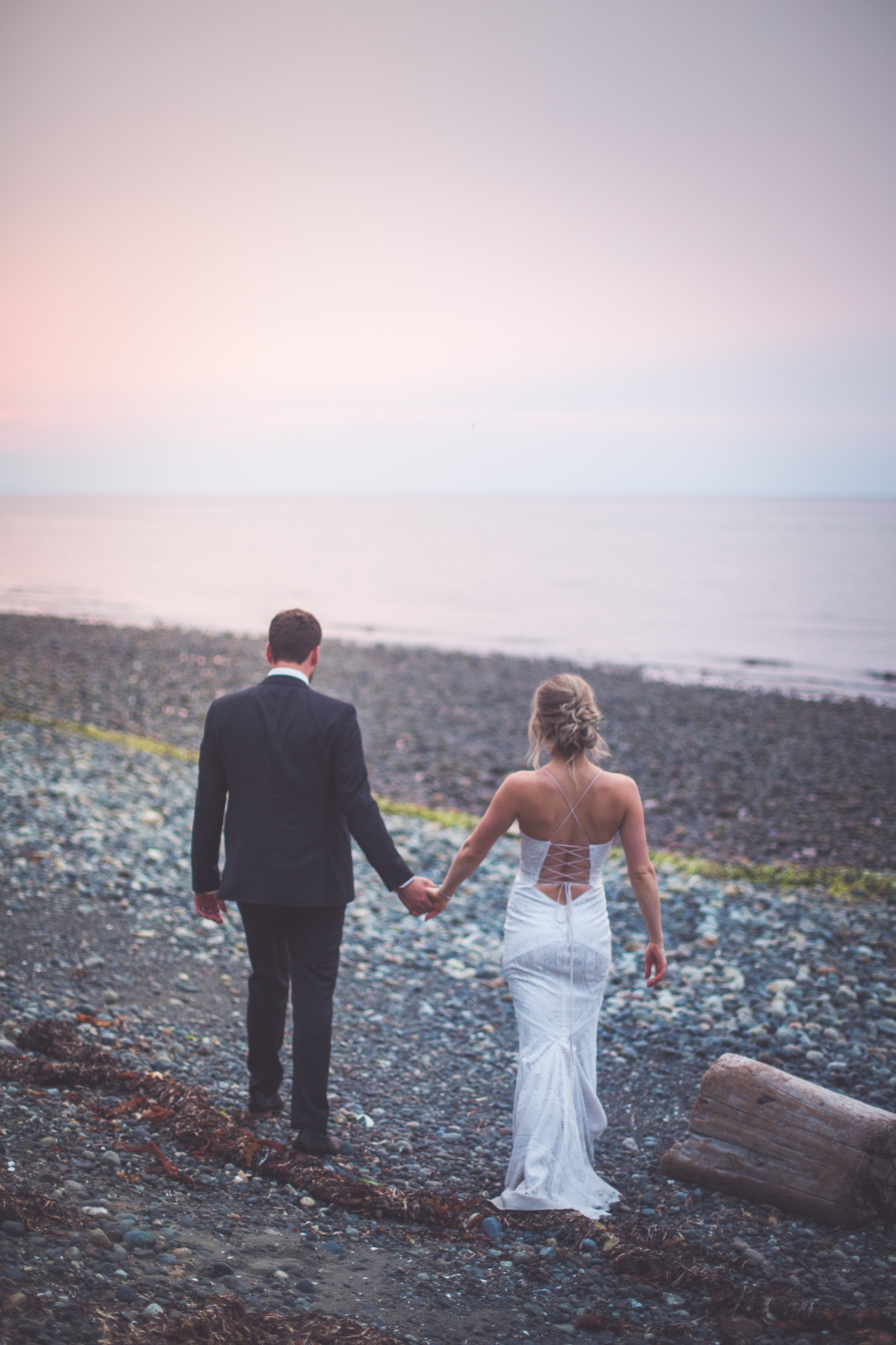 sunset portraits for bride and groom with smoke filled sky backdrop in Qualicum Beach