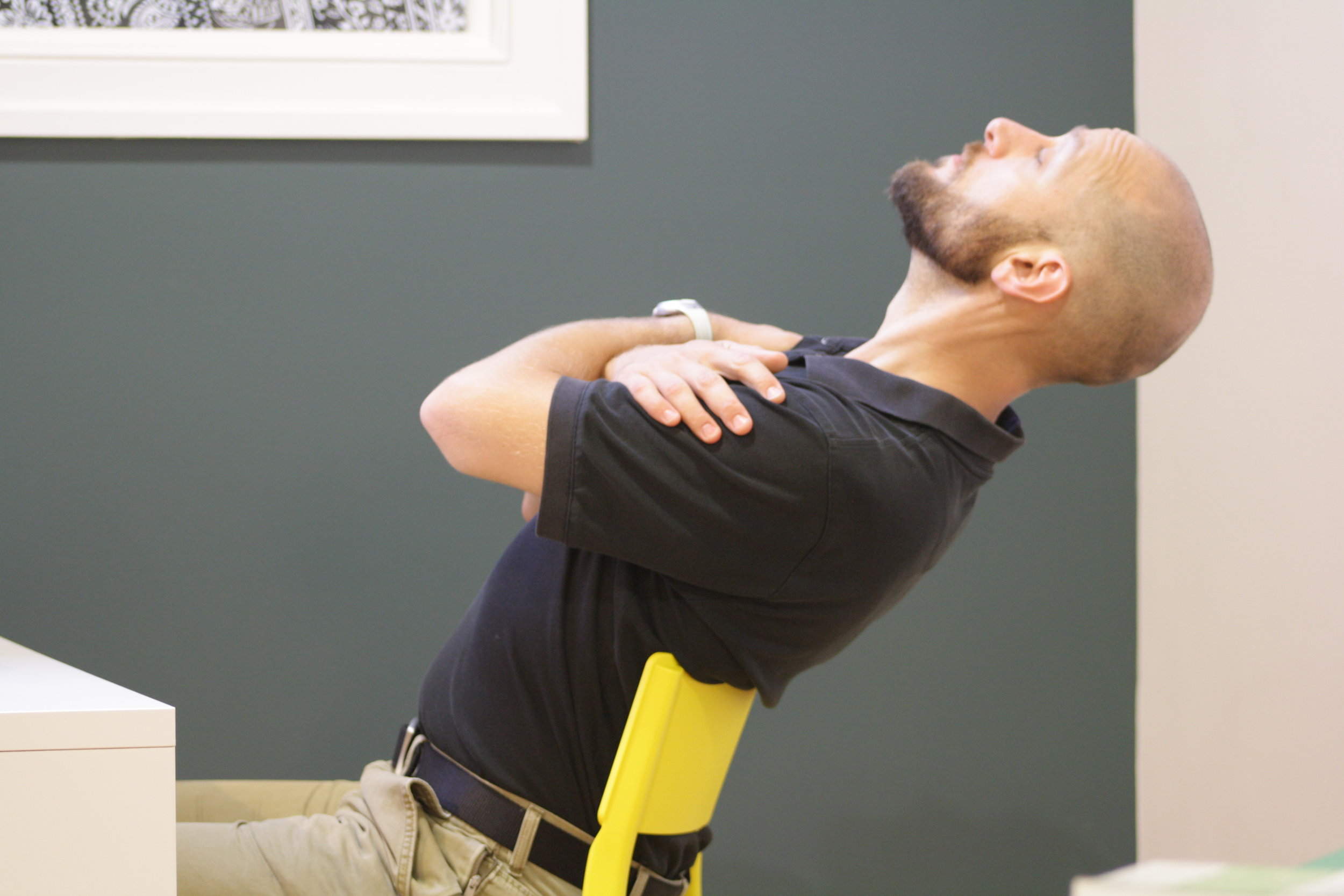 Seated extension over a chair-back can provide a good stretch to those with a tight back.