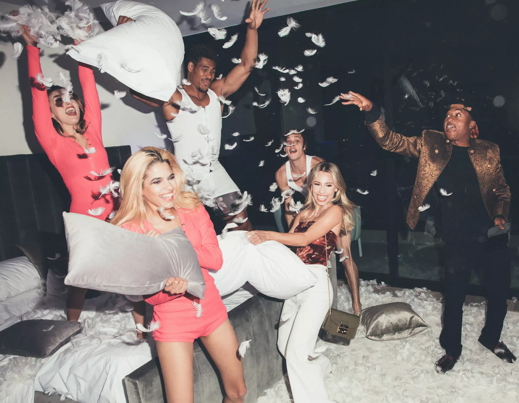 The Instagram influencer Ayla Woodruff, center, and Adrew Seally, right, get into a pillow fight with models. At this open house, setups were created to encourage social media posting.  Photo Credits: Adam Amengual for The New York Times
