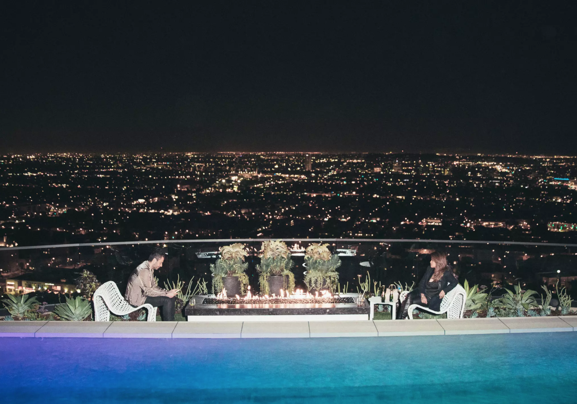 Guests enjoying their phones and the views by the pool at the open house at 1625 Woods Drive in Los Angeles.