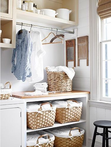 Cabinet shelving with no fronts and woven baskets for uniform storage.