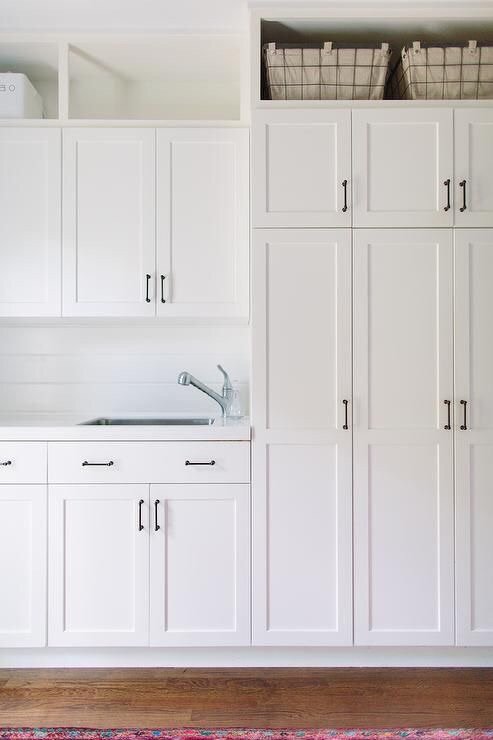 White shaker cabinet fronts with bronze hardware. Take storage to the ceiling to maximize space and free-up work surfaces.