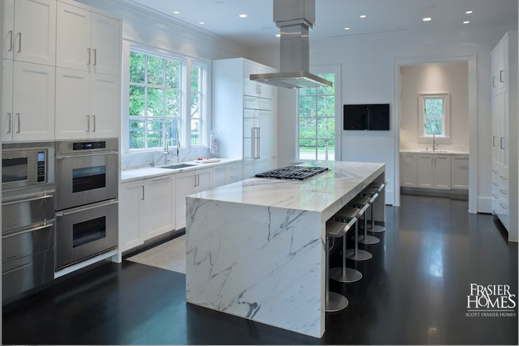 Kitchen features a sleek Calacatta marble island and stainless-steel Dacor, Sub-Zero, and Miele appliances.
